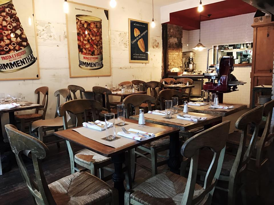 Fiaschetteria Pistoia's dining room has posters of canned goods on the wall and a wooden table in the middle