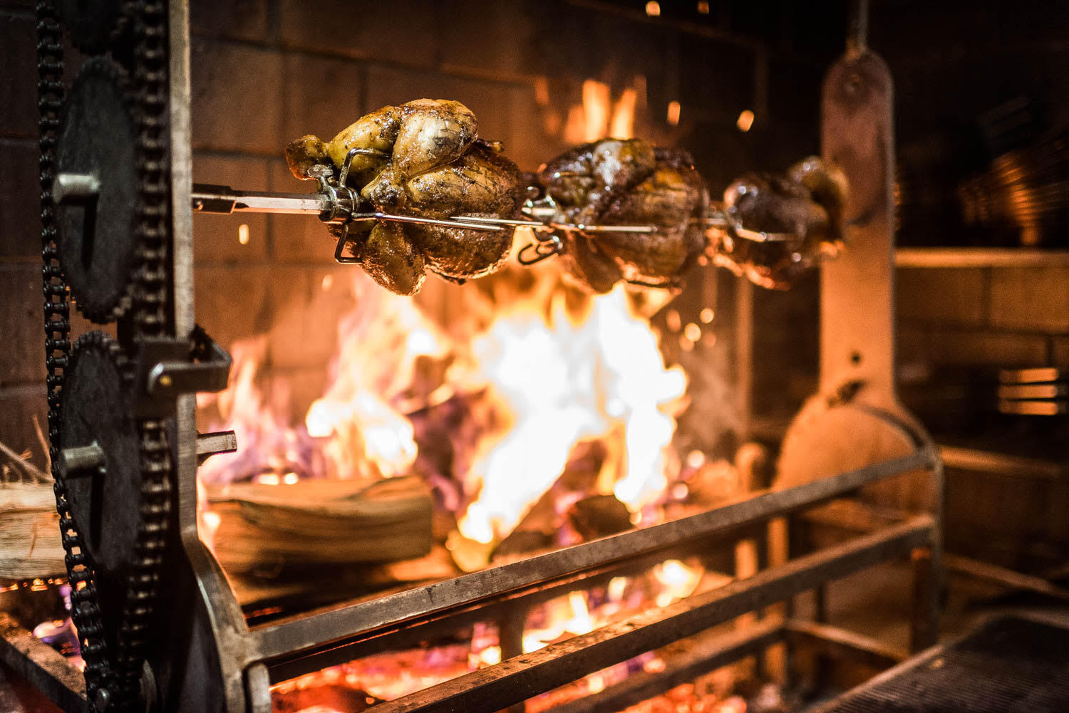 Honey-basted chicken cooking over the wood-fired hearth at A Rake's Progress.