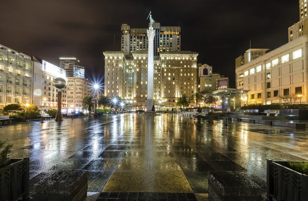 Union Square at night, with the ground wet from rain.