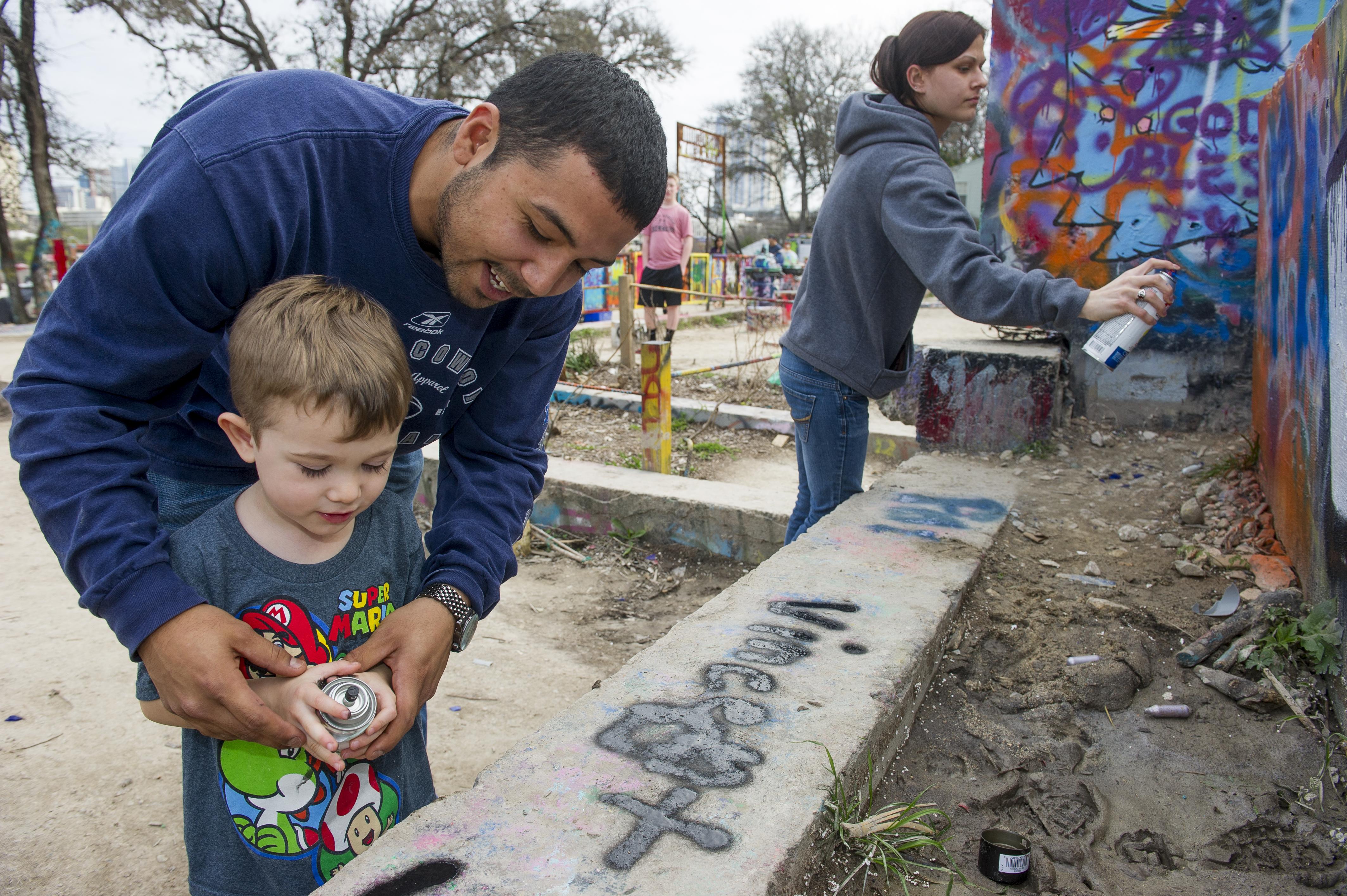 Man helping kid spray paint on graffiti park wall