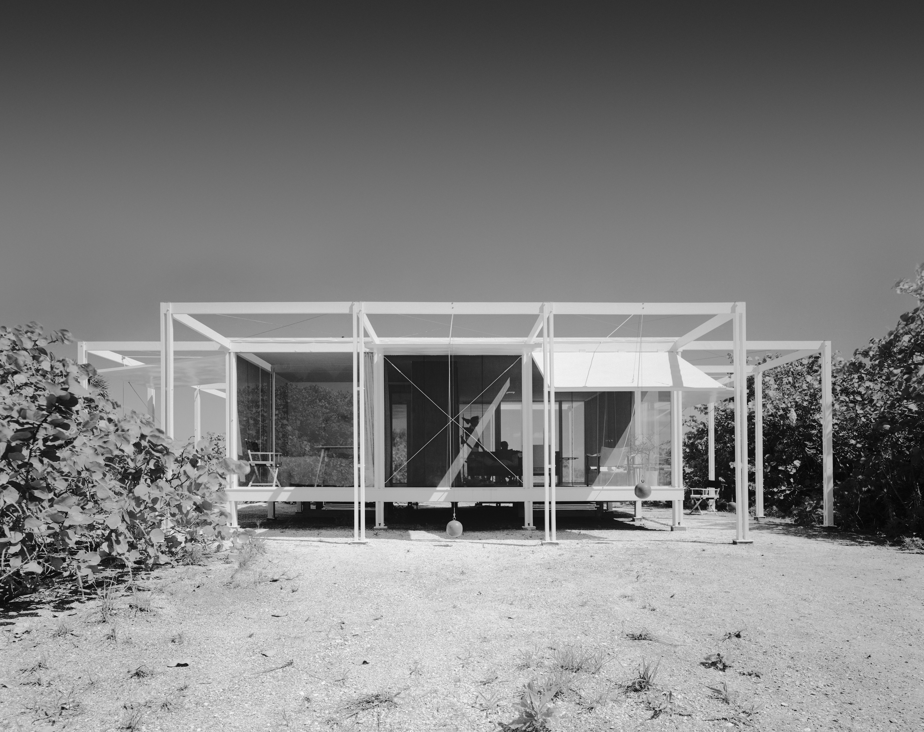 Low-slung modern guest house in black and white photo.