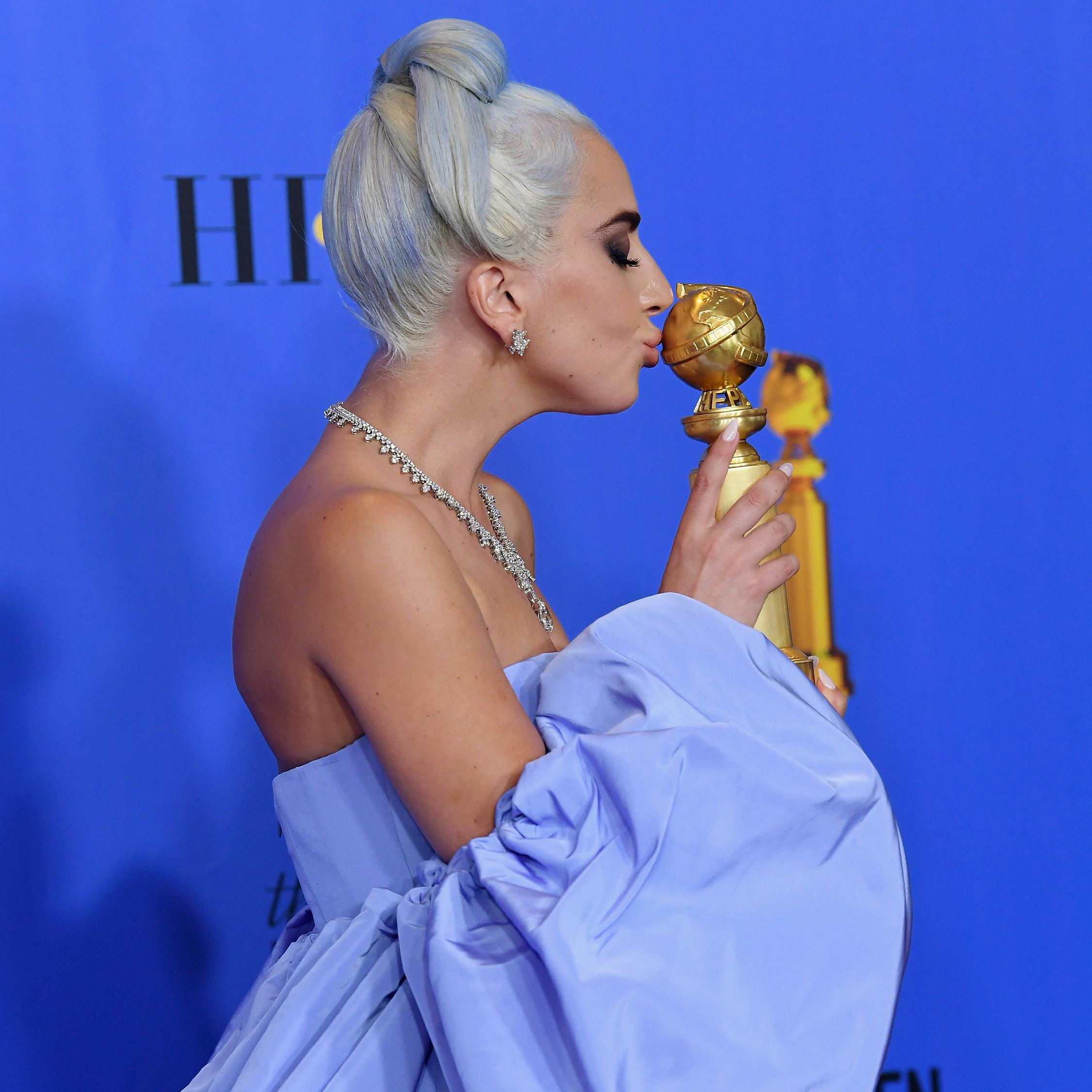 Lady Gaga kissing her Golden Globe statuette.