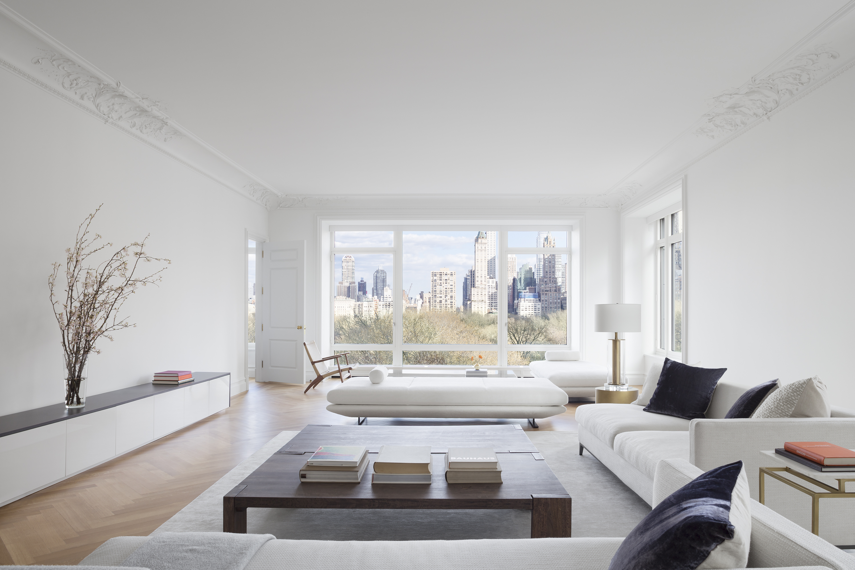 Living room. The walls are painted white. There is a white couch, a coffee table, a shelf with a plant in a planter, and large floor to ceiling windows on the far wall.