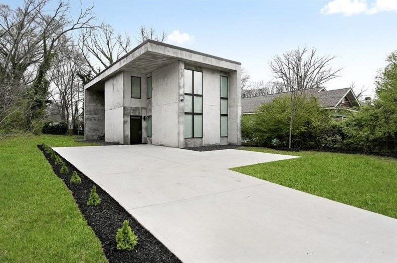 Two-story concrete house with long driveway.