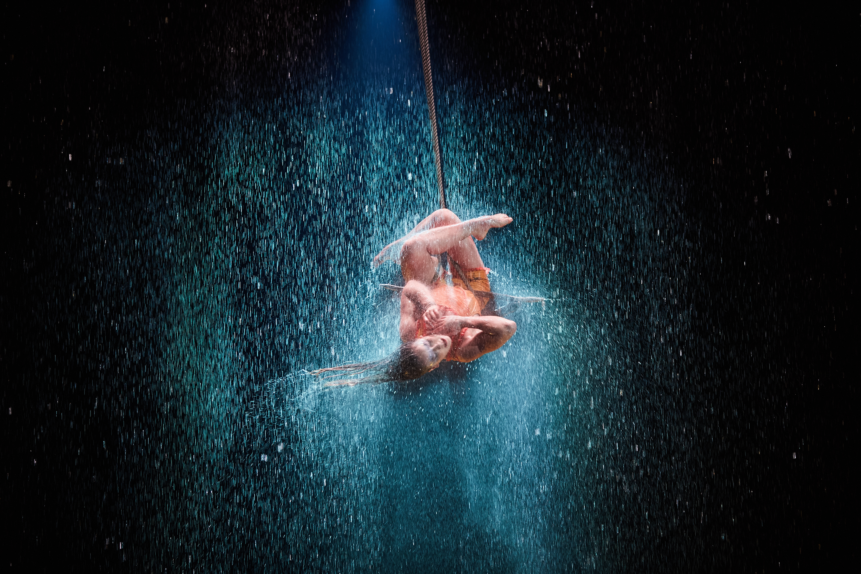A figure poses upside down, hanging from a rope, with legs crossed, in a torrential downpour.