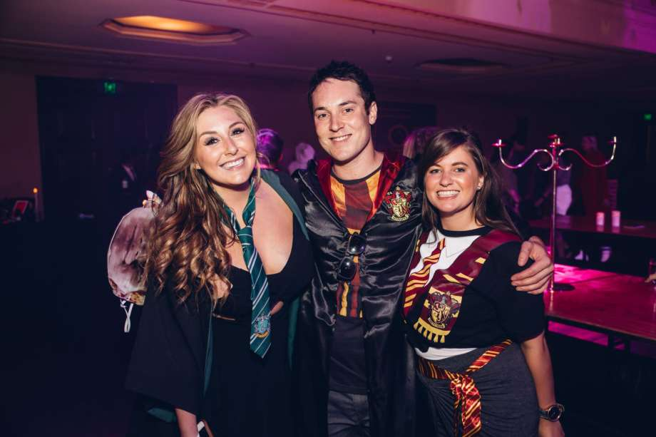 Three young adults in Harry Potter-style wizard costumes pose at an event