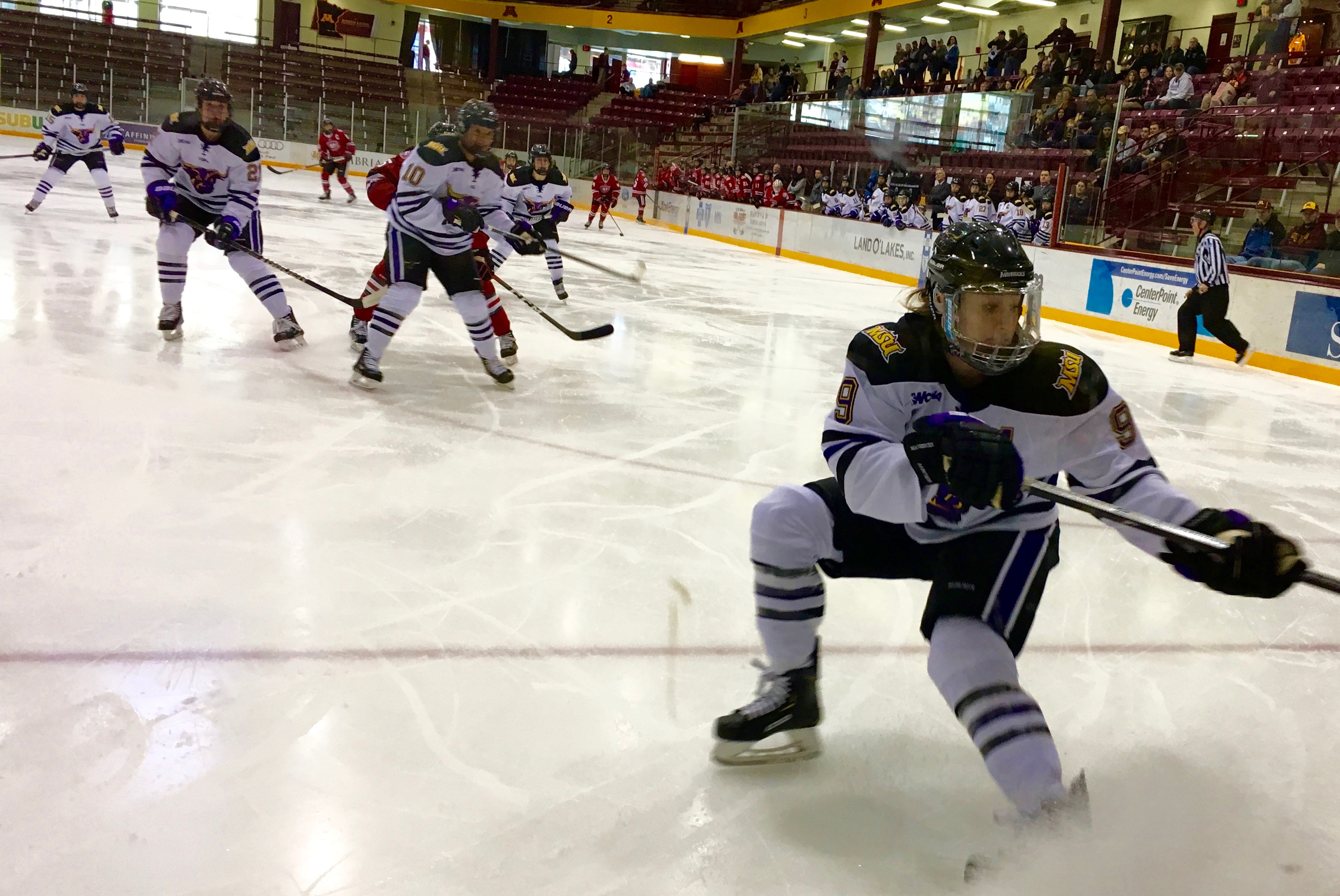 McKenzie Sederberg (#9) for Minnesota State reaching the boards and kicking up some ice in the process.