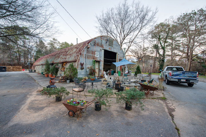 Metal building surrounded by flowers and a truck.