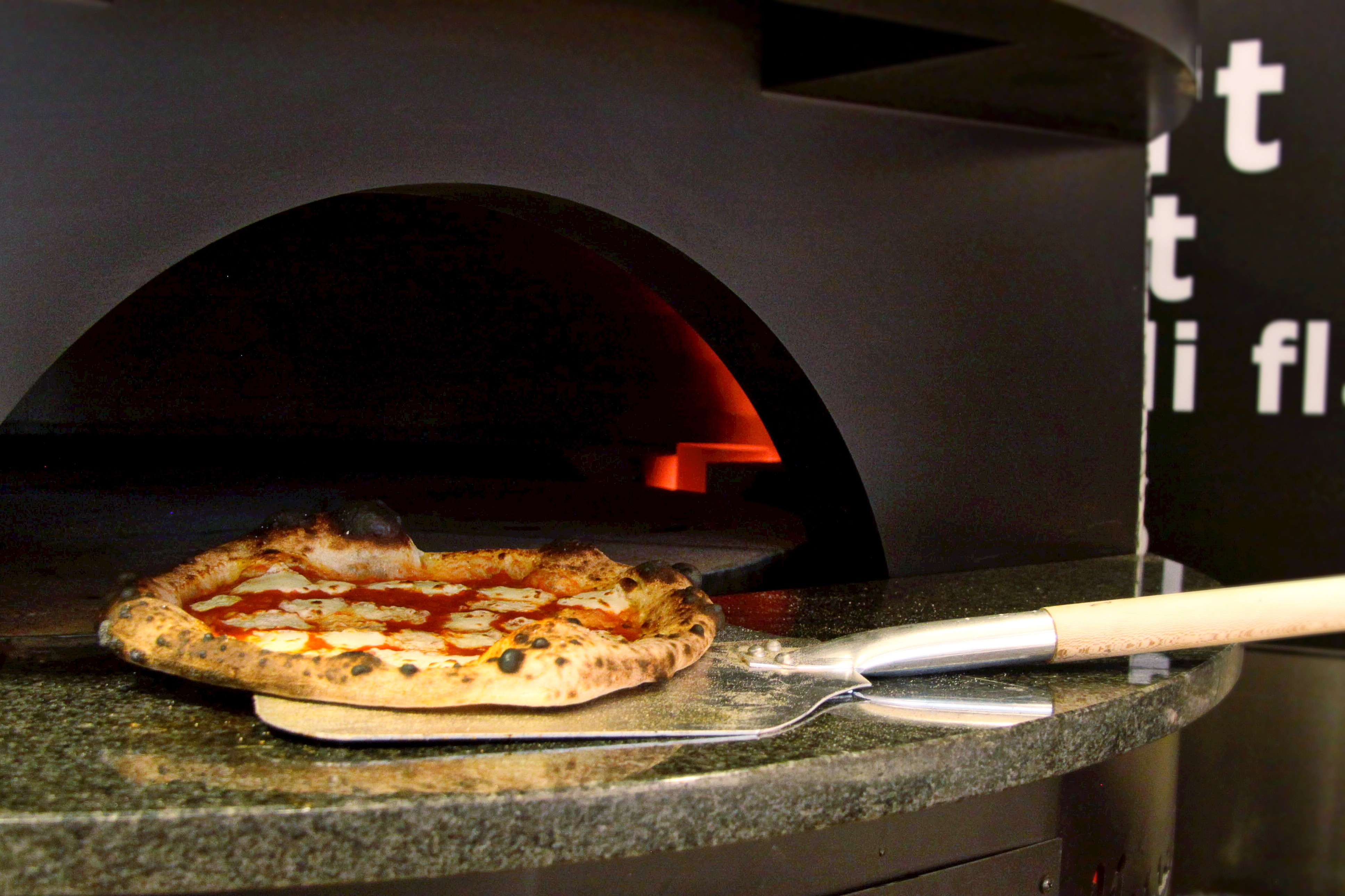 A pizza being pulled out of a pizza oven