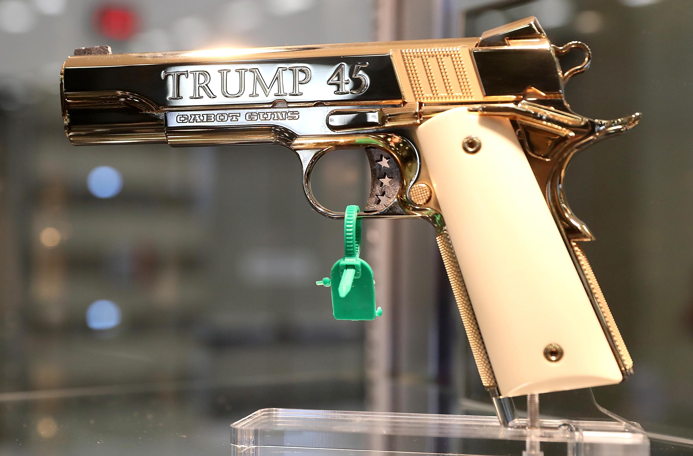 """A golden handgun that reads """"Trump 45"""" on the barrel."""