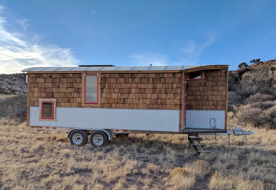 A small travel trailer in the desert. The trailer has a partially wooden facade.
