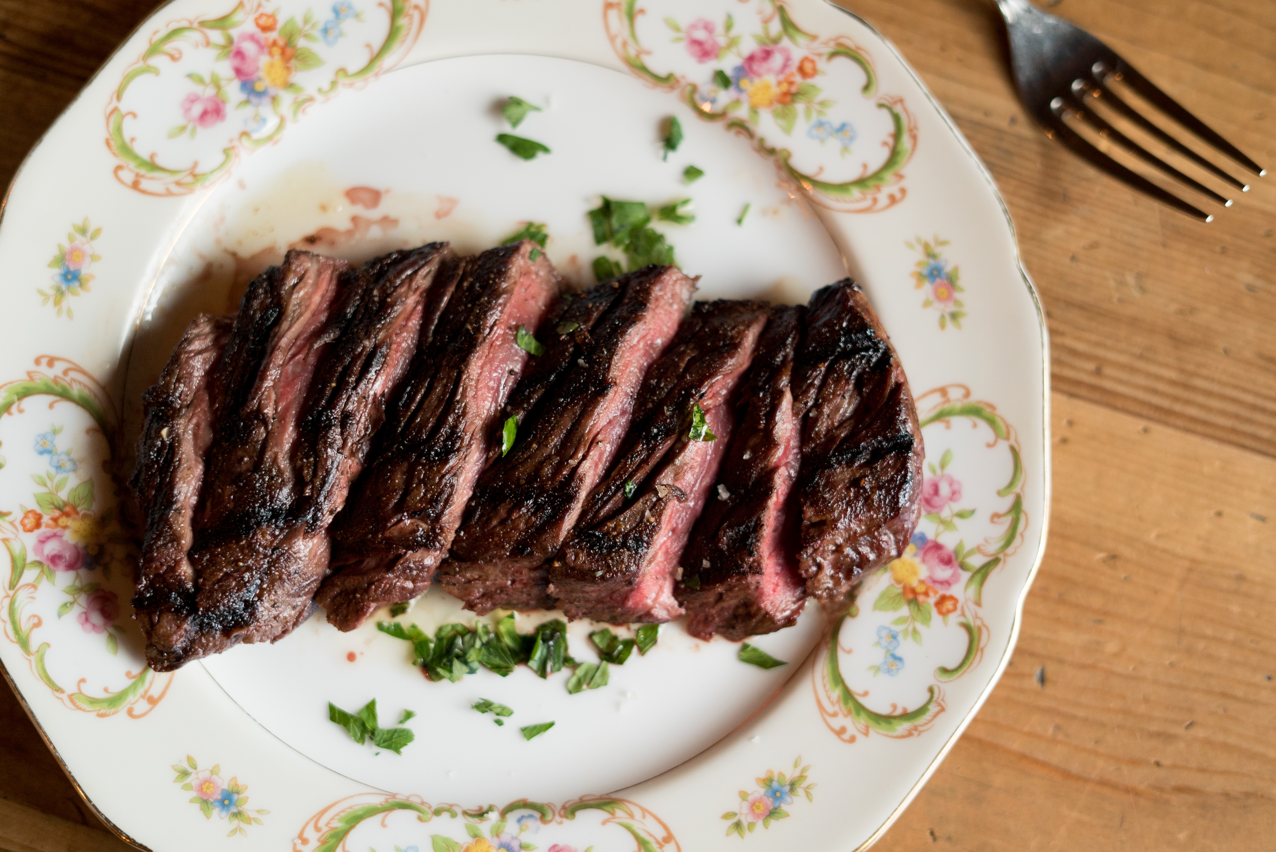 Slices of steak on a white plate with a floral design