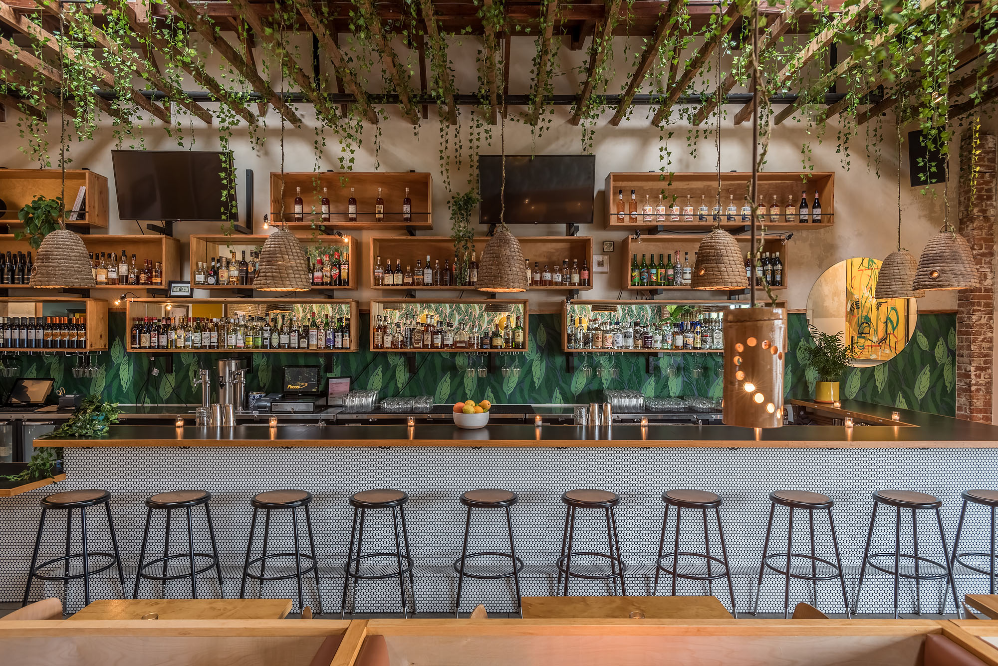 A lush and leafy bar with metal stools.