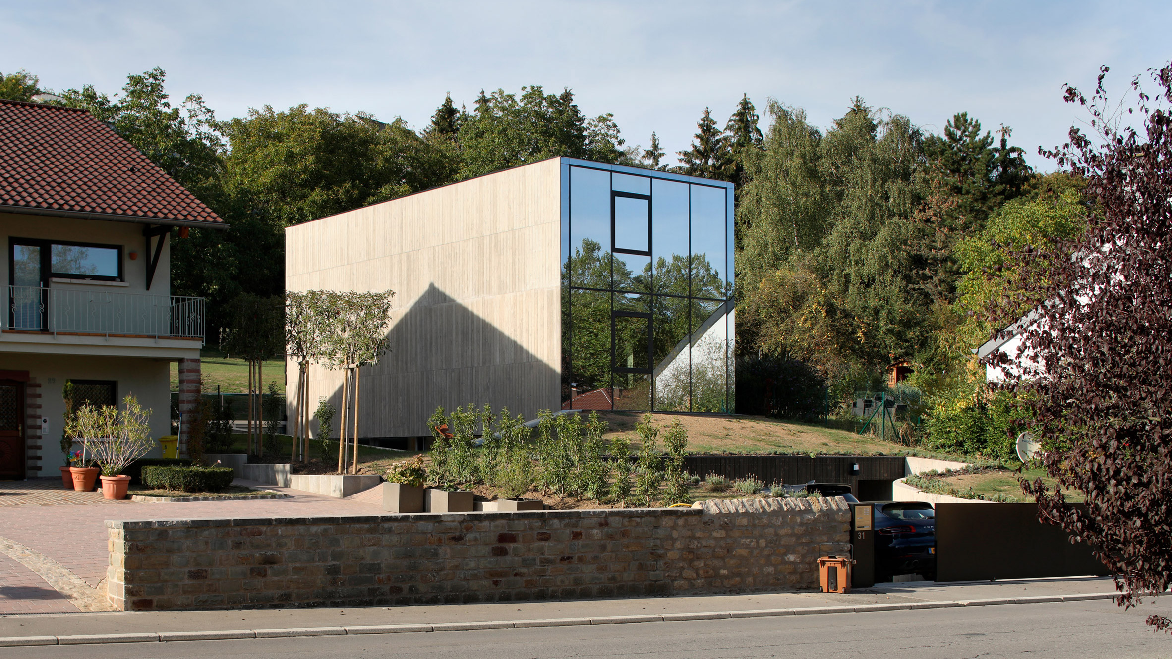 The exterior of a house which has concrete walls and a front facade which consist entirely of glass. The house is surrounded by trees.