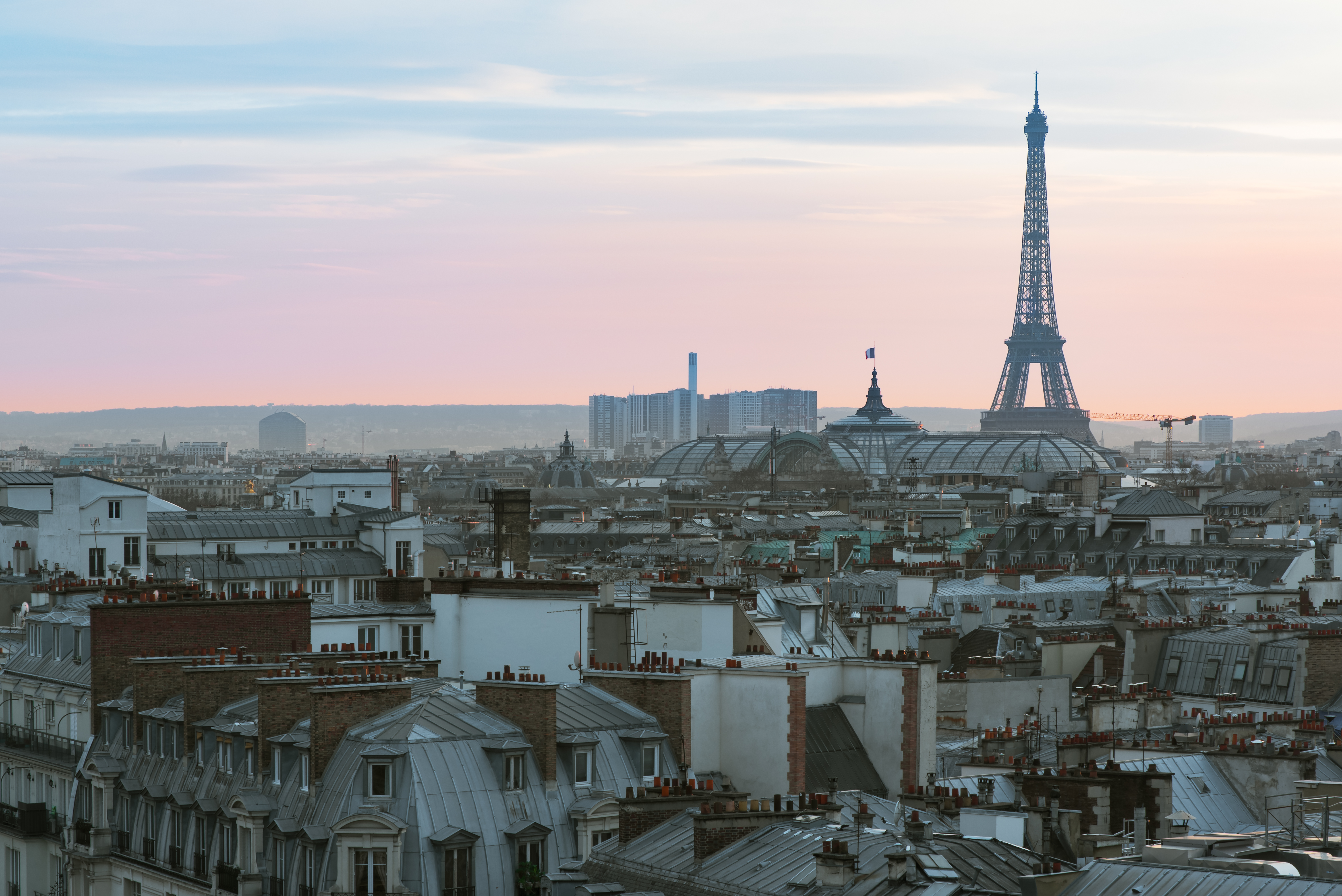 An aerial view of the city of Paris. There are various city buildings in the foreground. In the distance is the Eiffel Tower. There is a sunset in the sky.