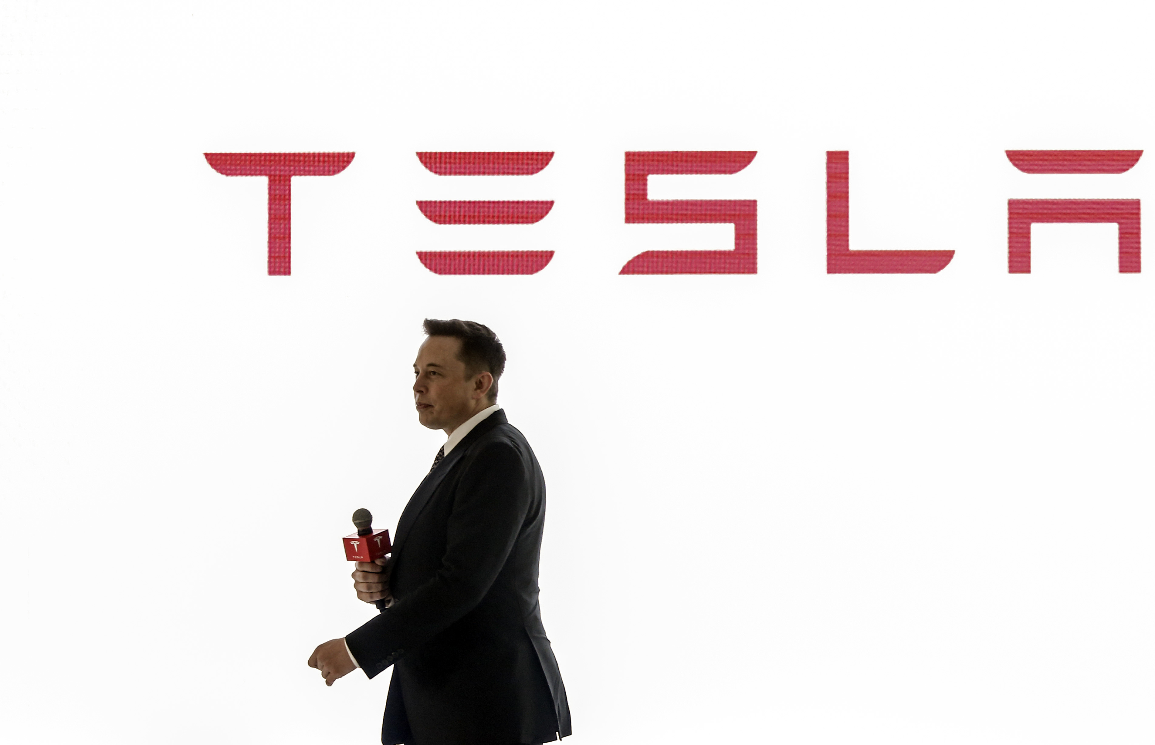 Tesla CEO Elon Musk in front of a Tesla sign