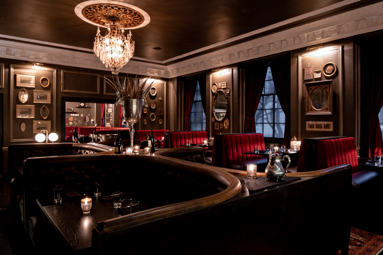 The dark dining room with a crystal chandelier, giant booths, with red velvet upholstery