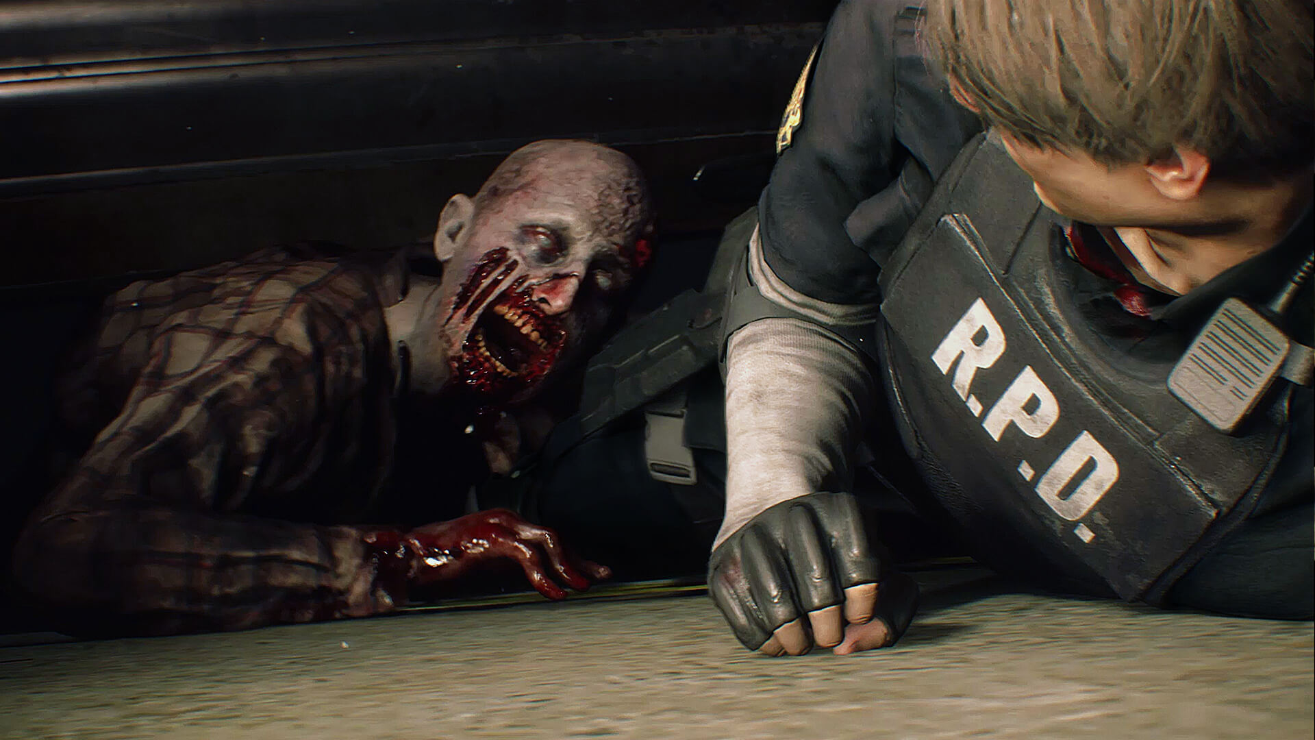 Resident Evil 2 (2019) - a zombie attacks Leon Kennedy on the ground