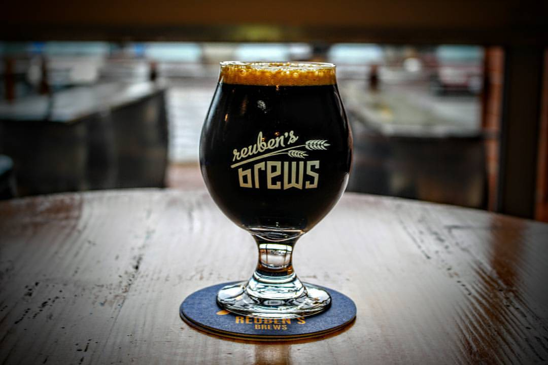 A dark beer with the Reuben's Brews name on the glass.