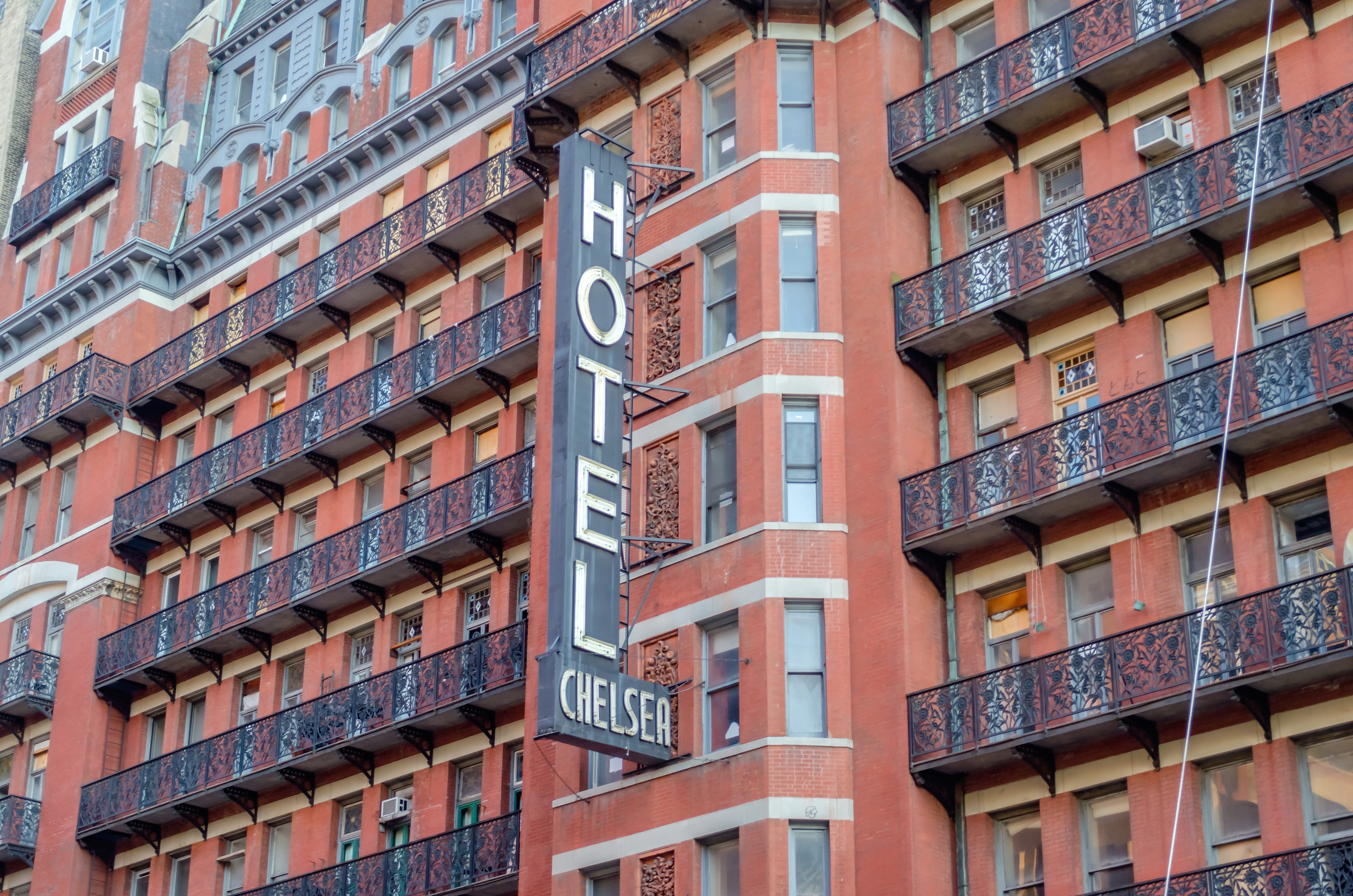 The exterior of Hotel Chelsea in New York City. The facade is red brick and there is a large sign that reads: Hotel Chelsea. There are black balconies in front of multiple exterior windows.