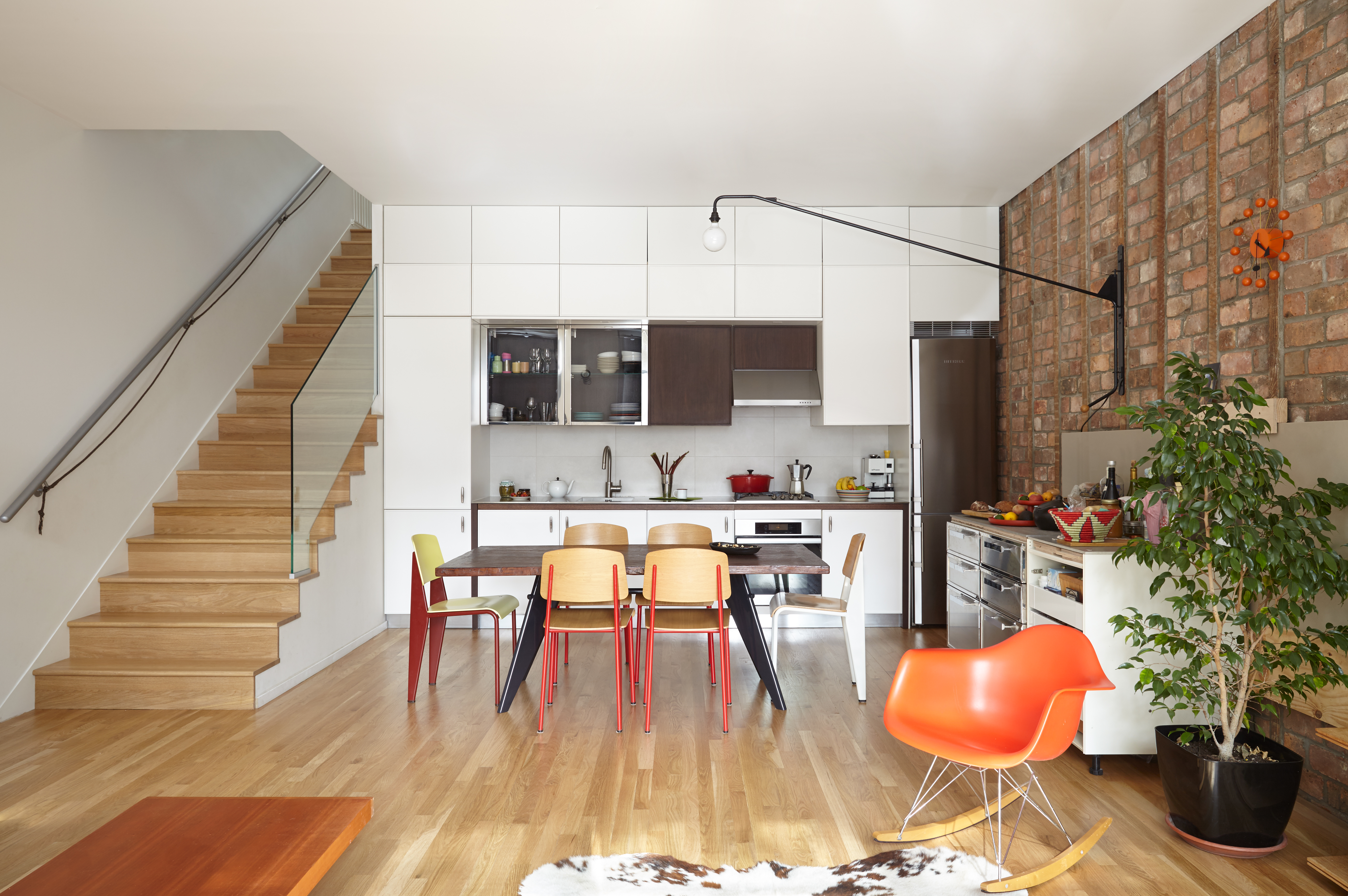 A living area. There is a table flanked by assorted chairs. There is white kitchen cabinetry. On one side of the room is a wooden staircase. On the other side of the room is an exposed red brick wall.