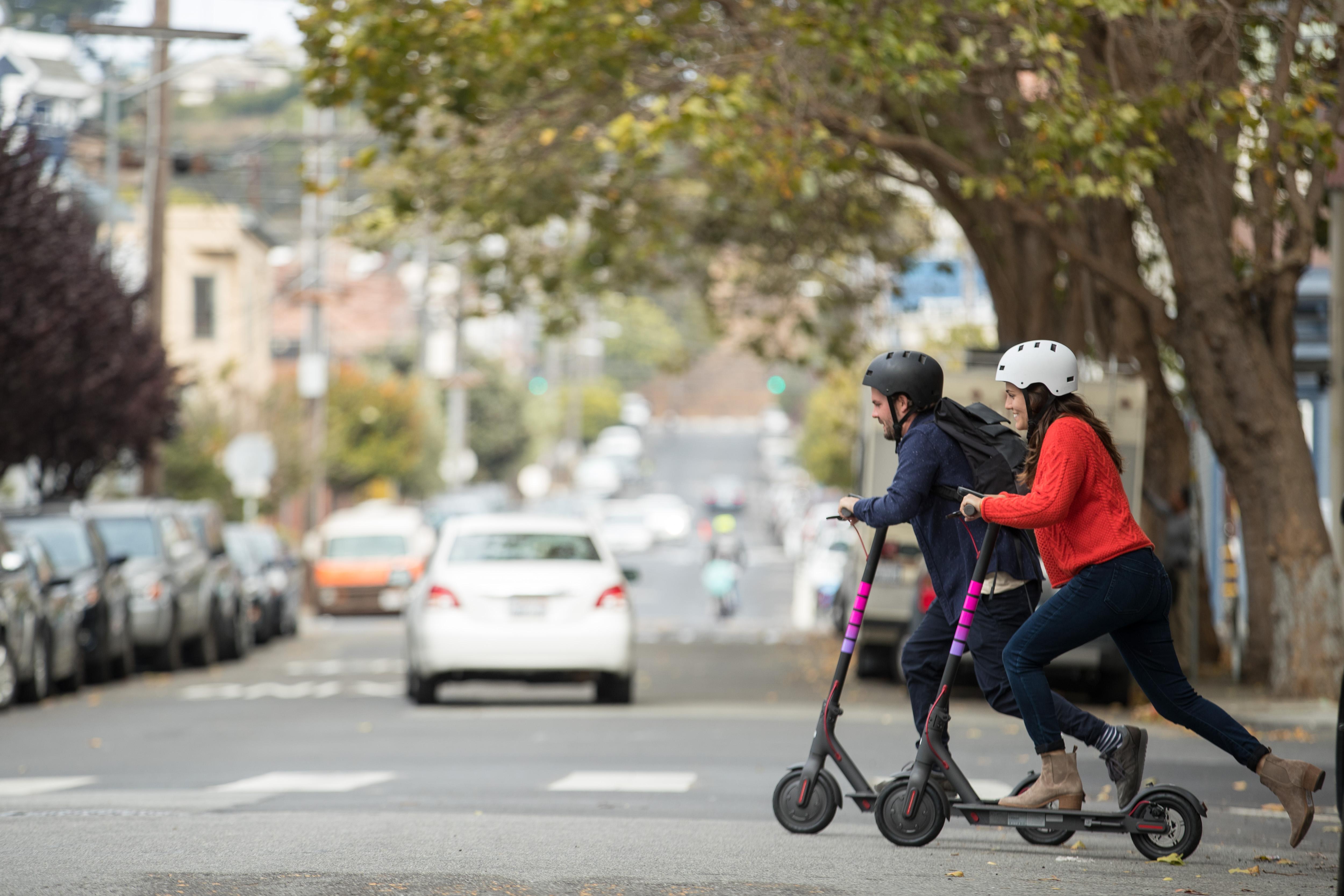 two people on Lyft scooters crossing a street