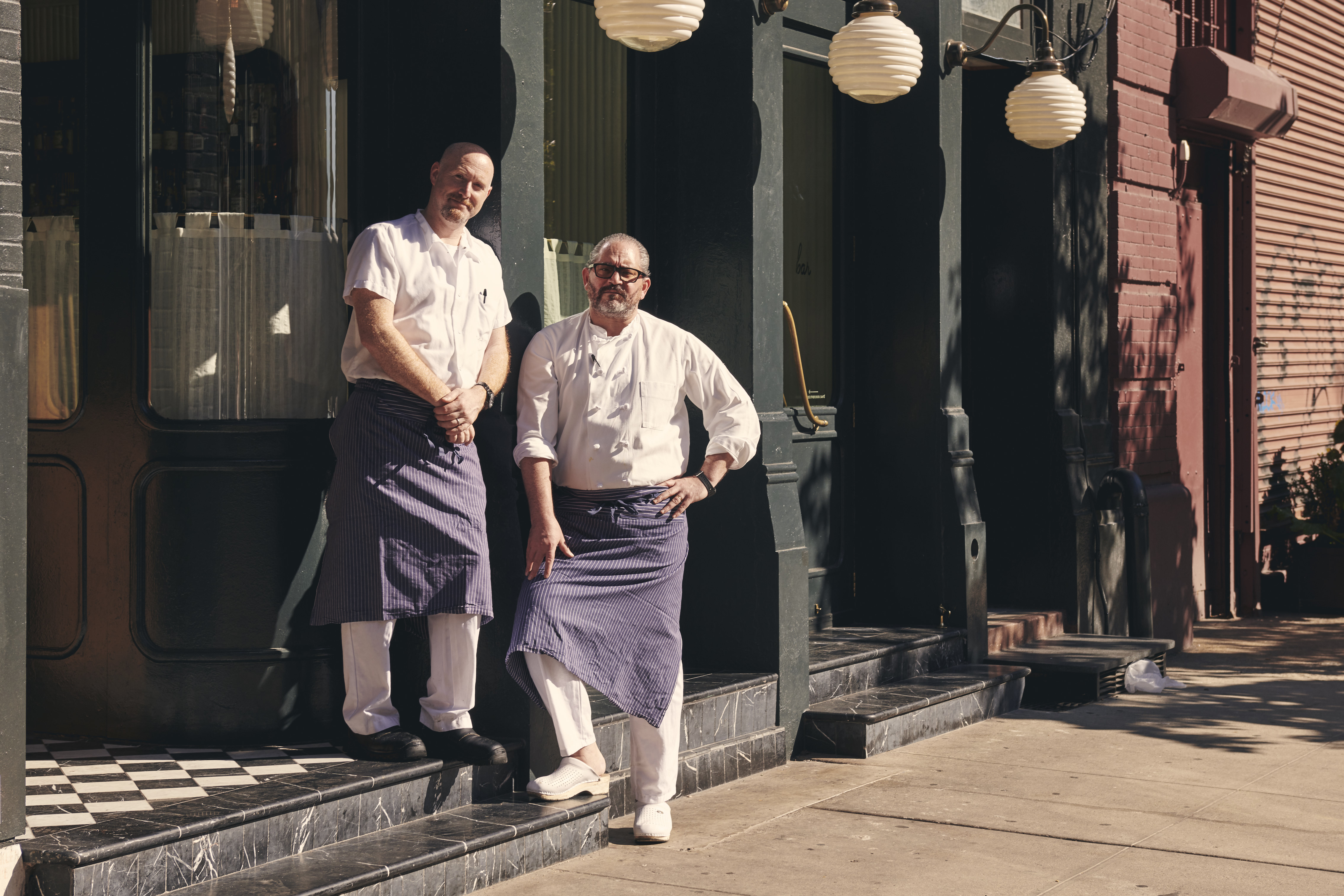 Chefs Lee Hanson and Riad Nasr stand in front of Frenchette, a restaurant that has a black painted front