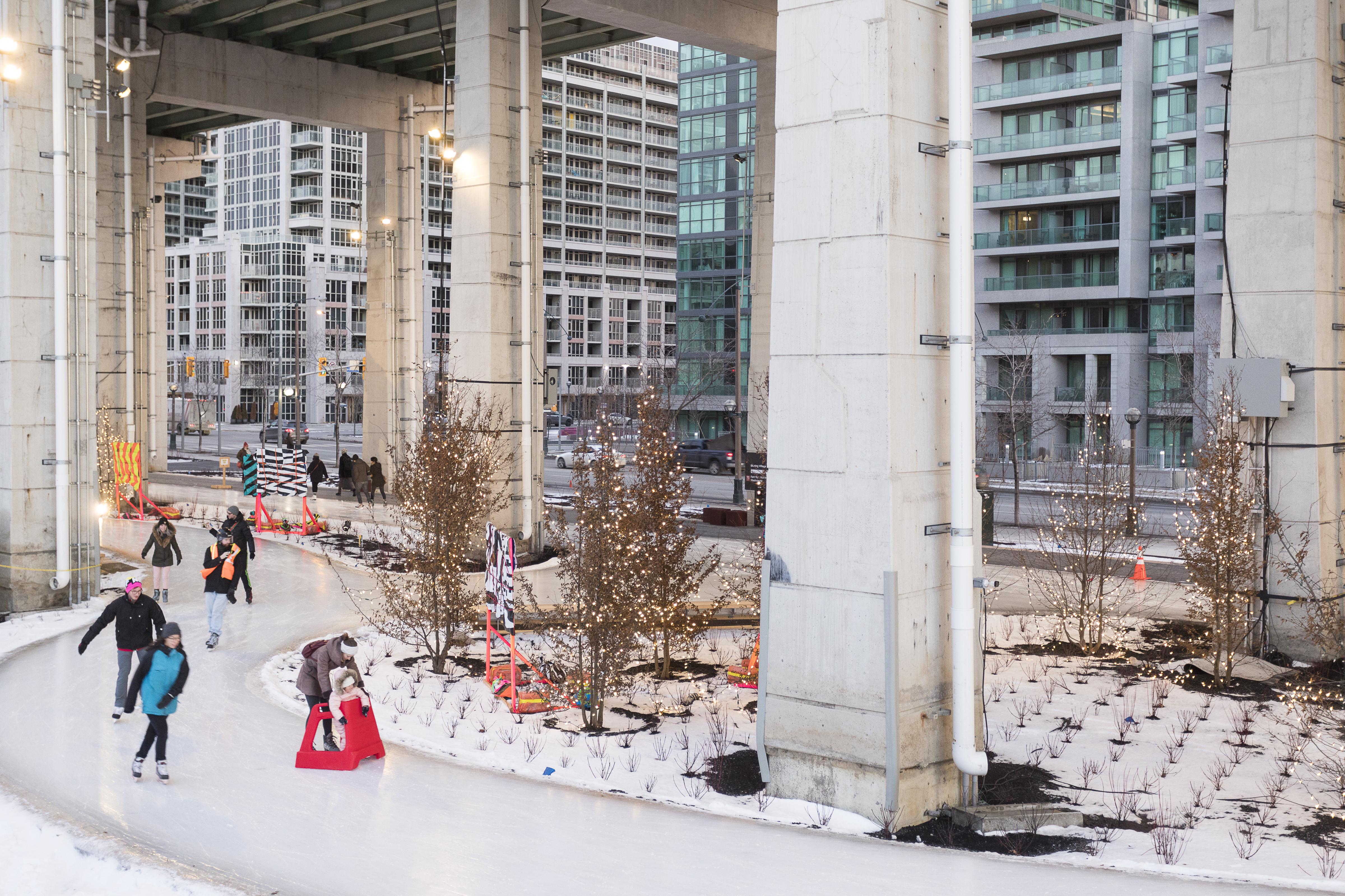 People ice skate along an ice path which is near a building with structural columns.
