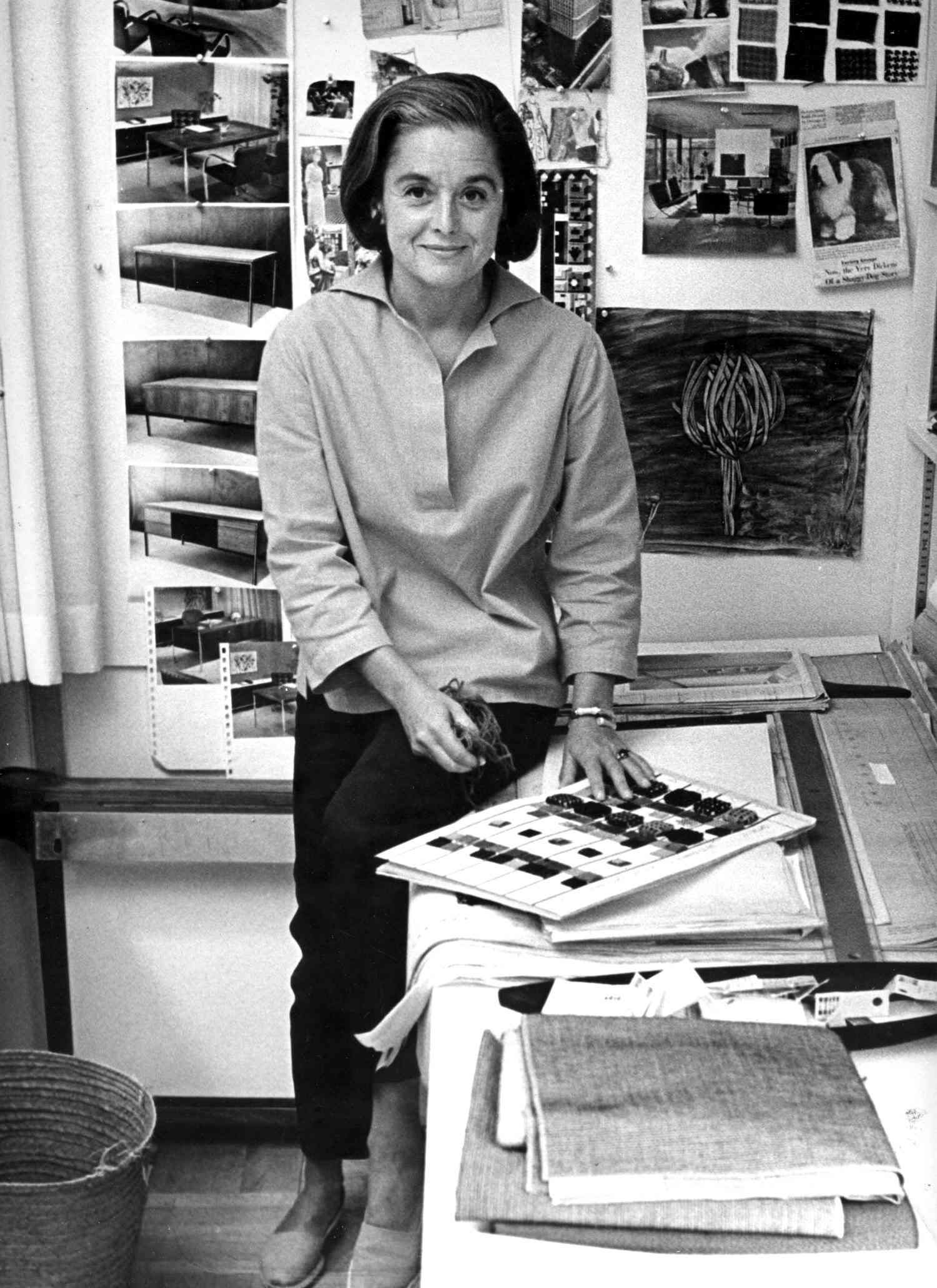 Portrait of American architect and furniture designer Florence Knoll Bassett as she sits on the edge of a table with a book of fabric swatches in front of her, 1961.