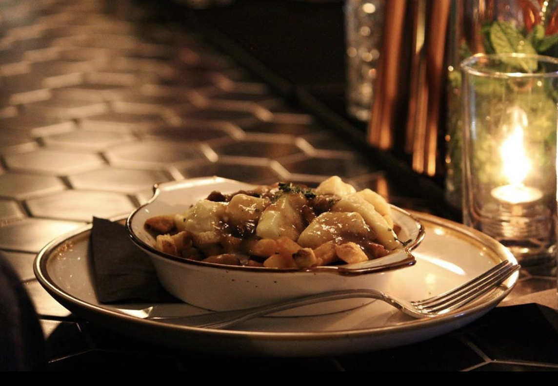 A low lit table at Olmstead shows off a plate of poutine, with Beecher's cheese curds and mushroom gravy.