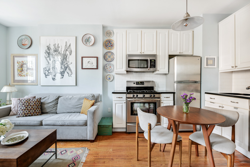 A living area with light blue walls, a small kitchen with white cabinetry, a round, wooden dining table, and a grey couch on the left side.
