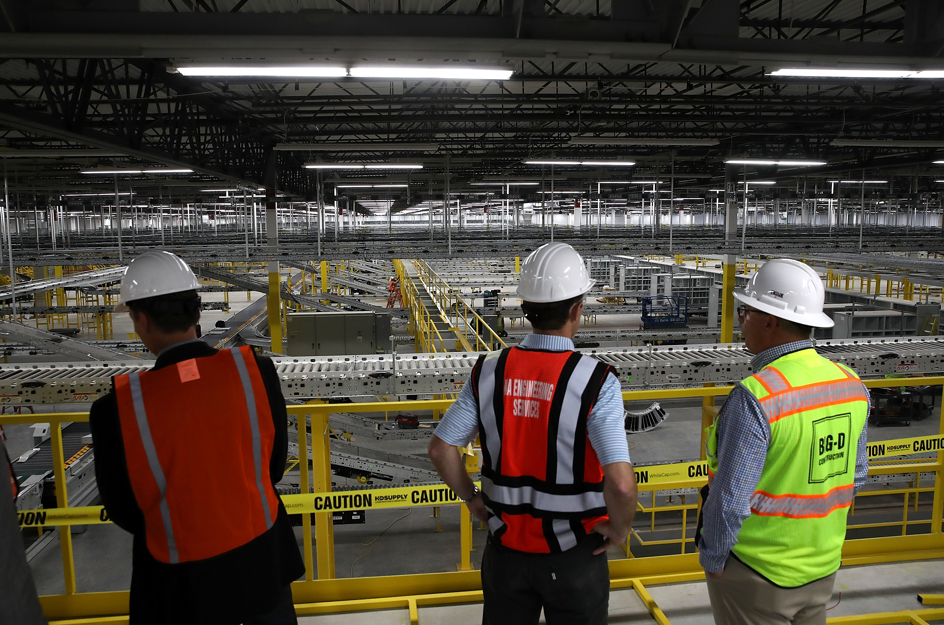 Workers in hardhats and neon vests view a conveyor belt system that is under construction at a new Amazon fulfillment center in Sacramento.