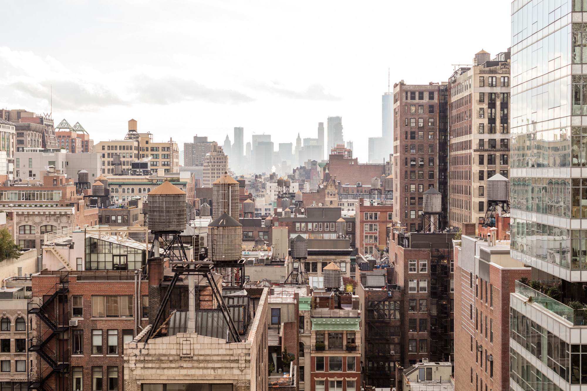An aerial view of New York City buildings on a hazy day.