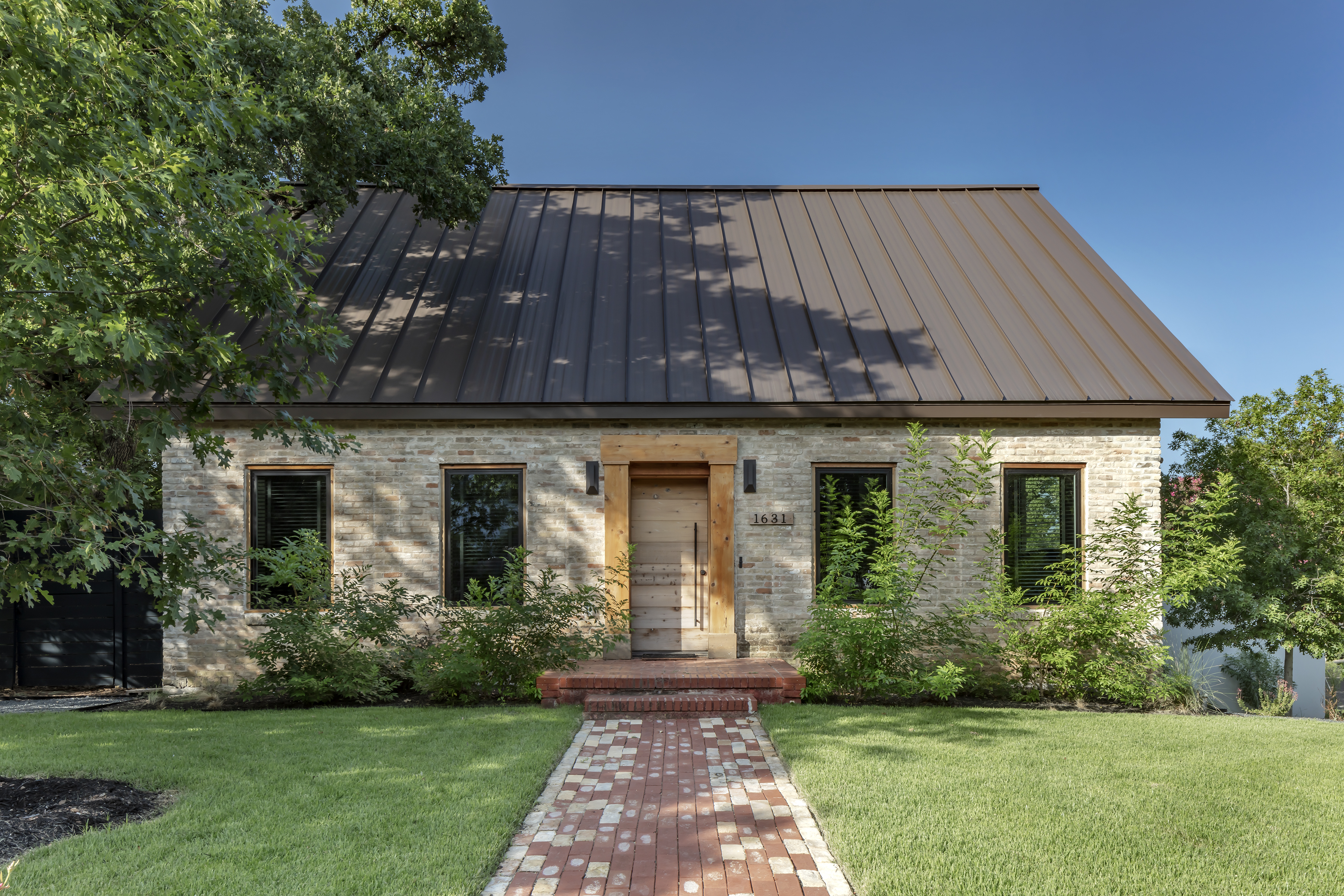 one-story 1938 stone home with new metal roof