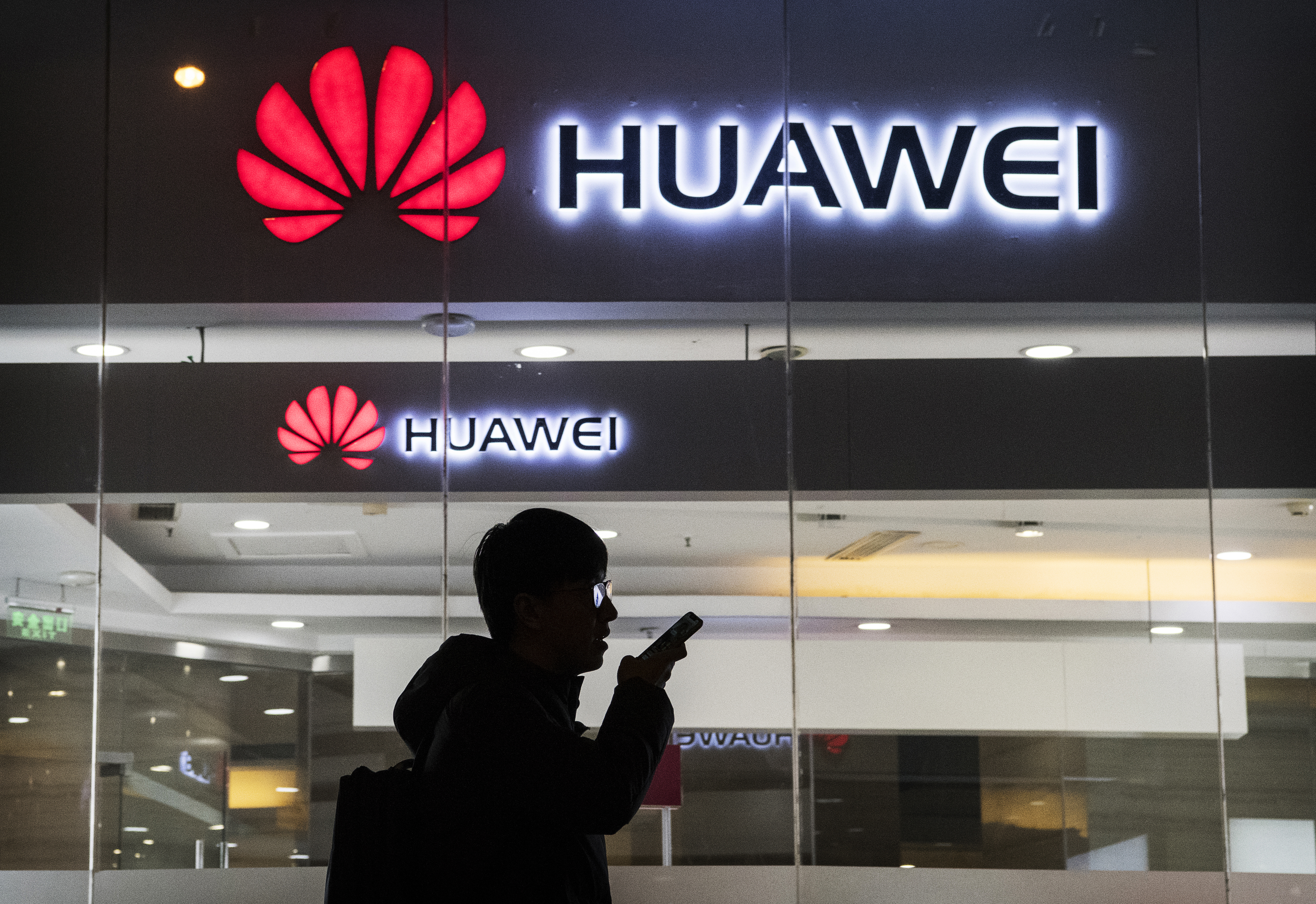 A man silhouetted against a glass storefront with a sign reading Huawei above it.