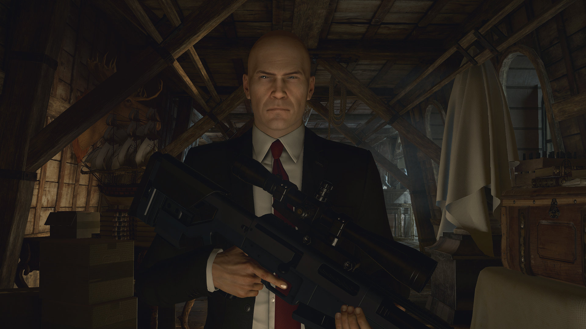 Agent 47 walks toward the camera, armed with a rifle, in a screenshot from Hitman.