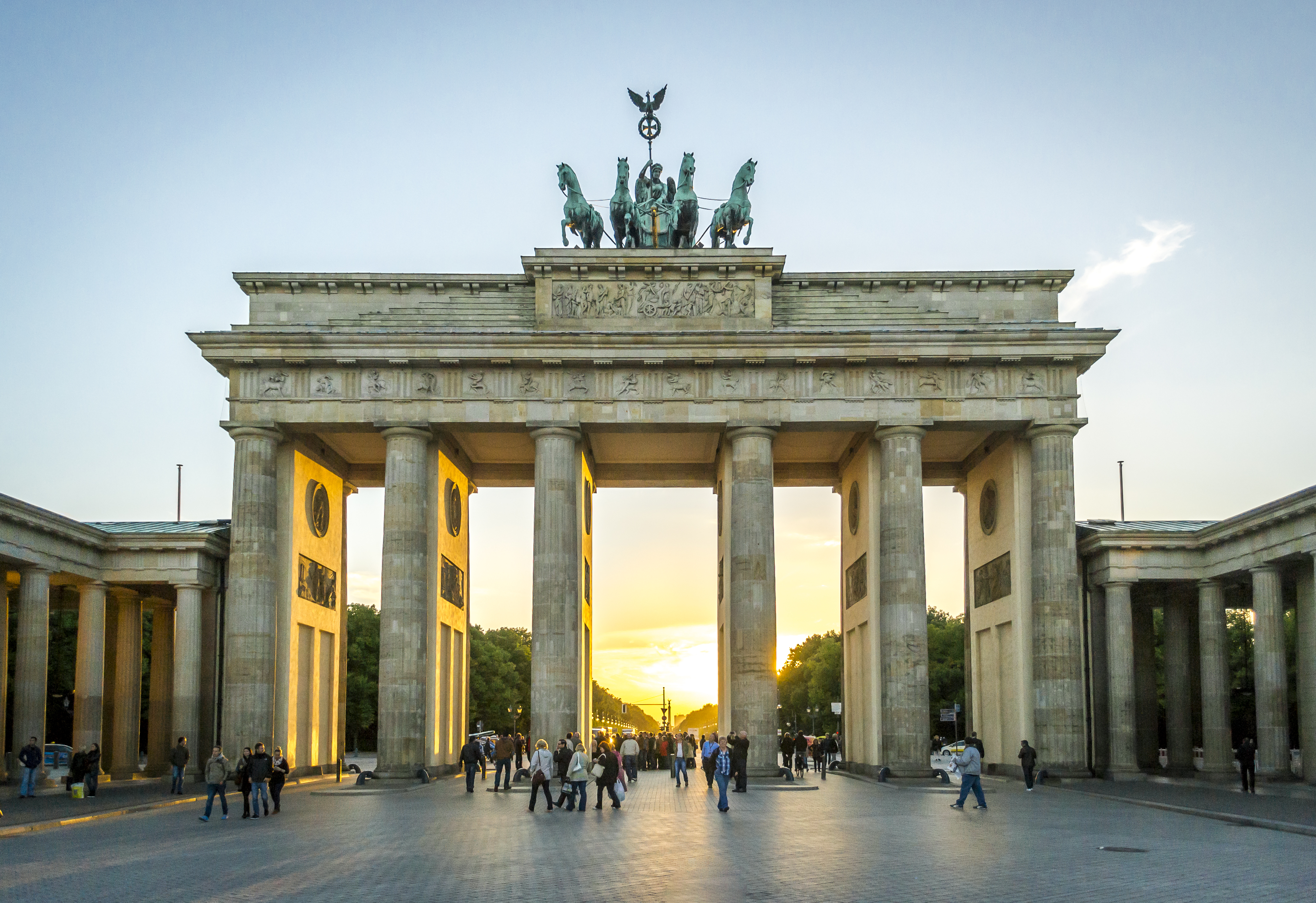 The exterior of the Brandenburg Gate in Berlin, Germany, at sunset. The gate has columns. There are statues on top of the gate.
