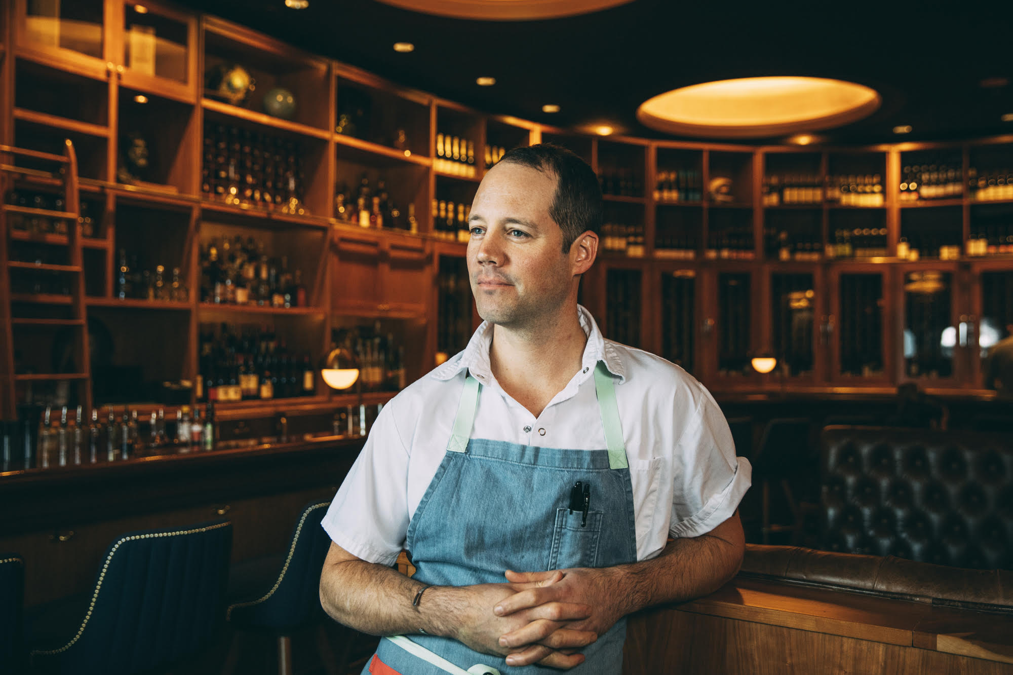 A white man in a white shirt and blue apron.