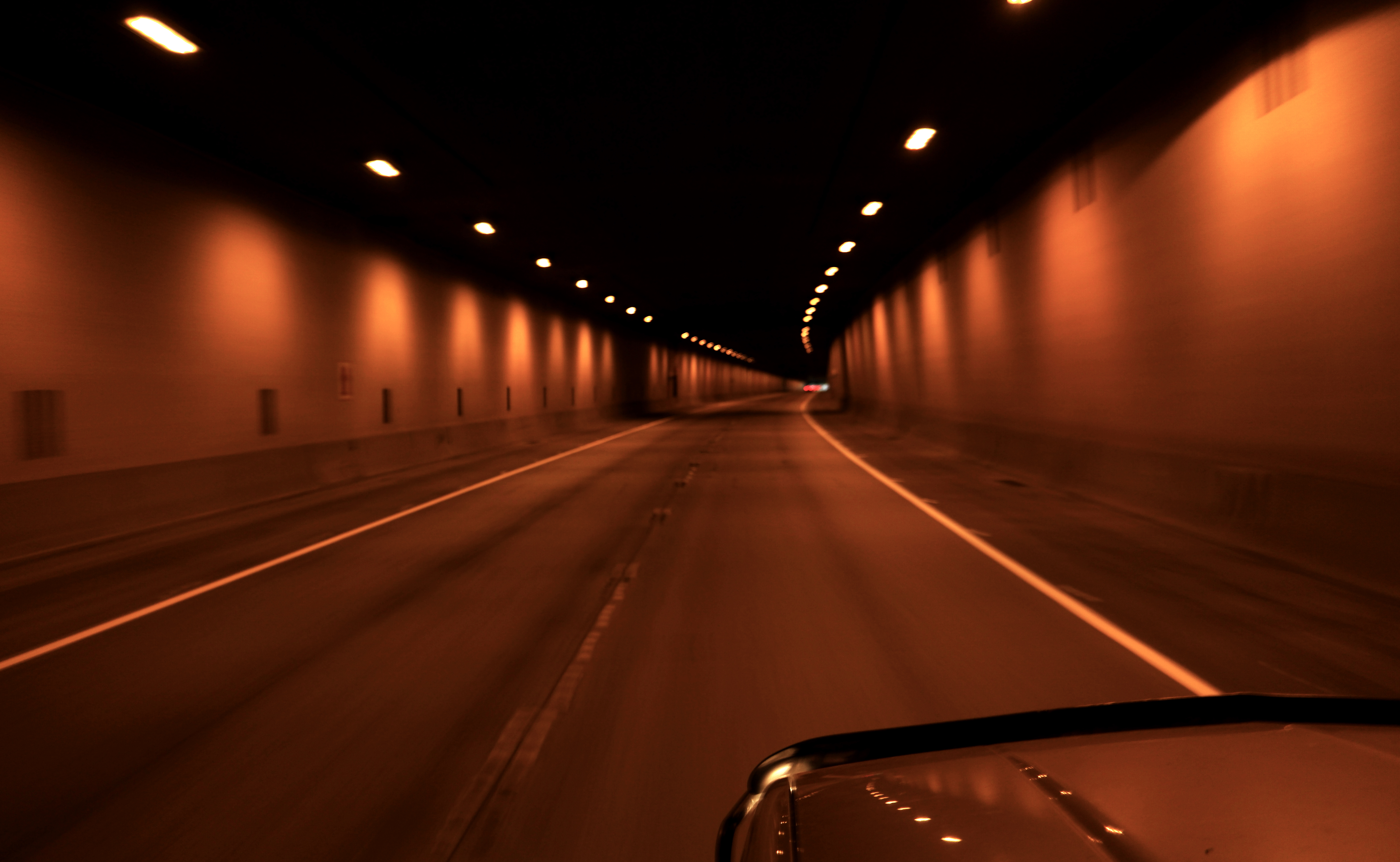 A dark tunnel with two traffic lanes, a white dashed line down the center, and a yellow solid line on either side. On the ceiling, two rows of lights give the tunnel a warm glow.