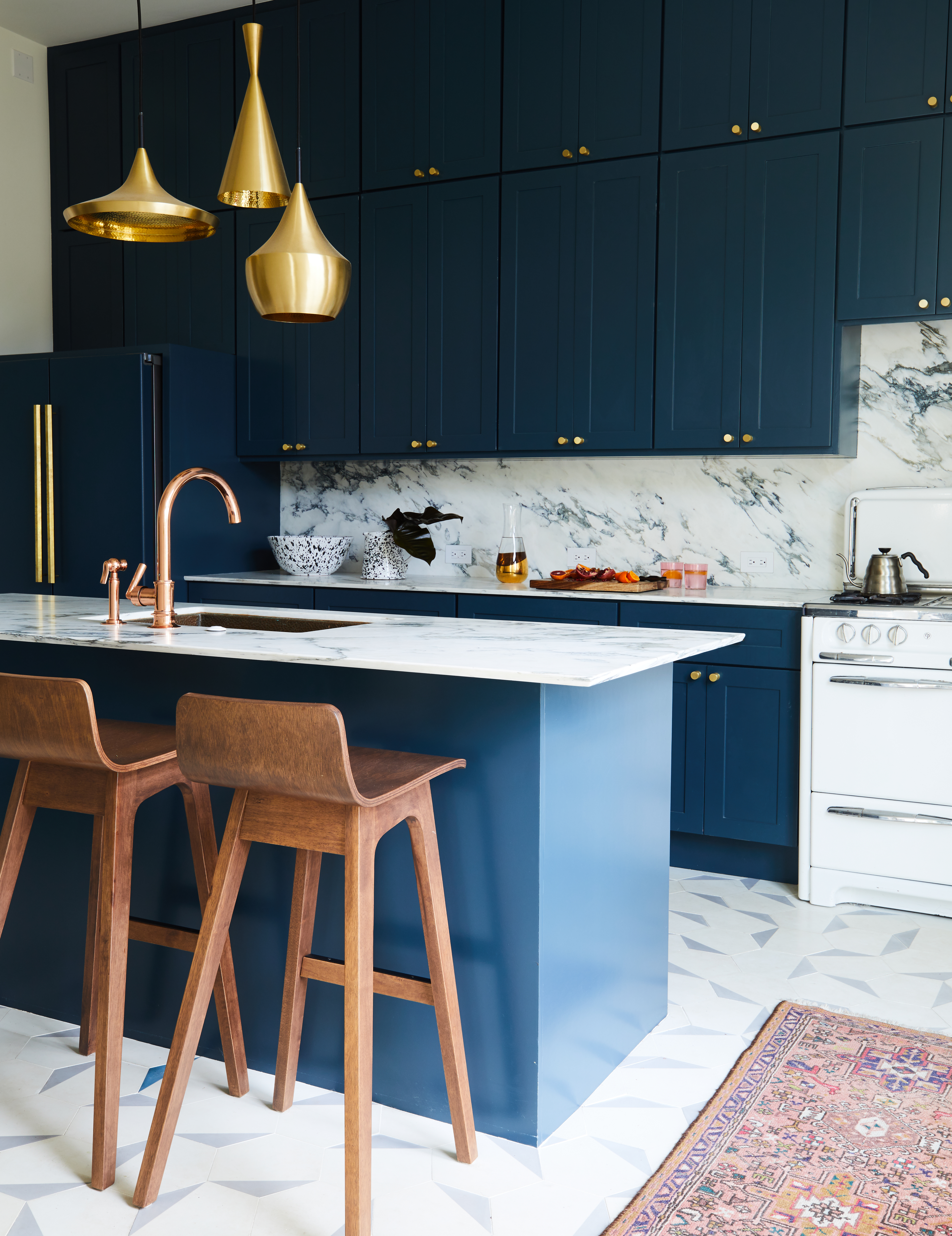 A kitchen with navy cabinets, brass fixtures, and brass lights dangling from the ceiling.