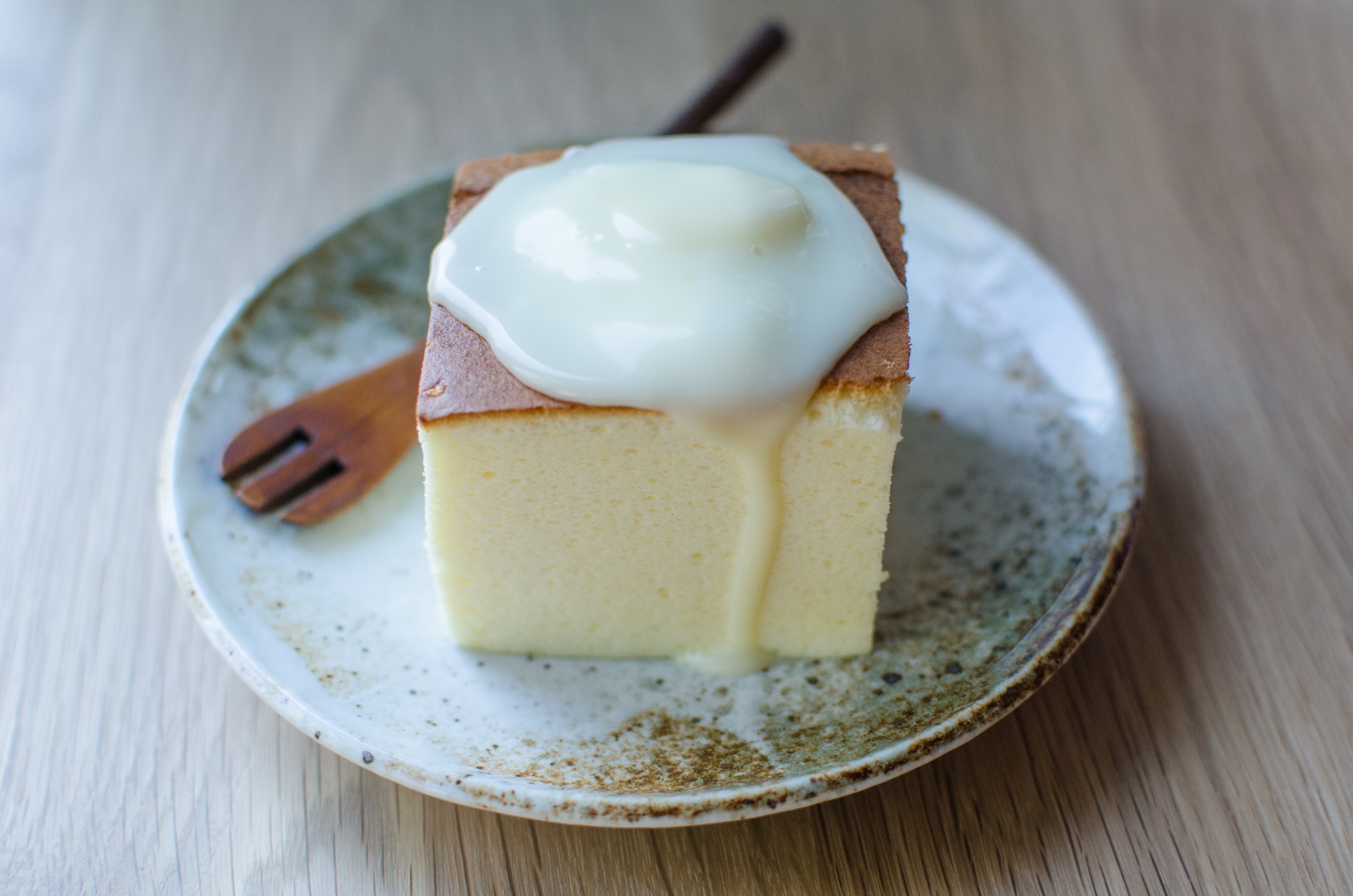 A slice of fluffy Japanese-style cheesecake sits on a speckled blue-ish plate, topped with a dollop of drippy cheese. A small wooden fork sits on the plate.