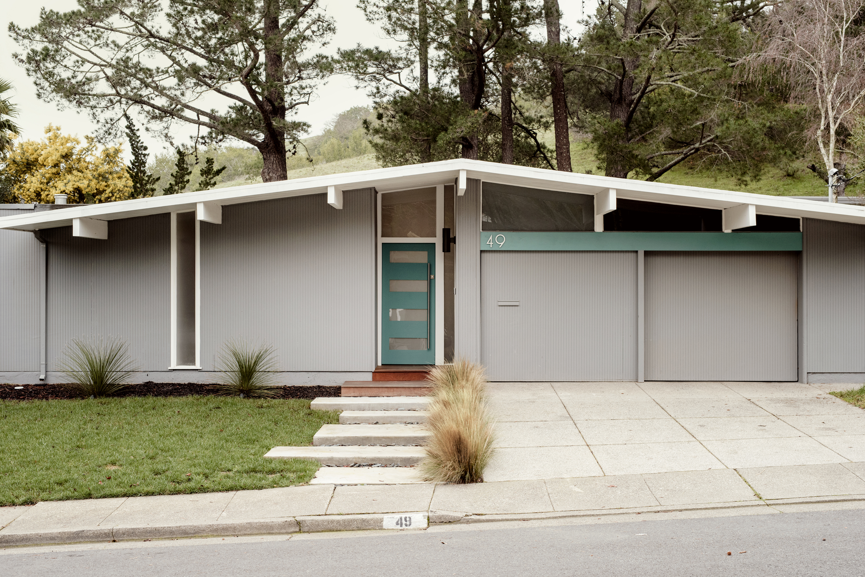 The exterior of a house which is painted grey. The door is green. There is a lawn in front of the house. There are trees in back of the house.
