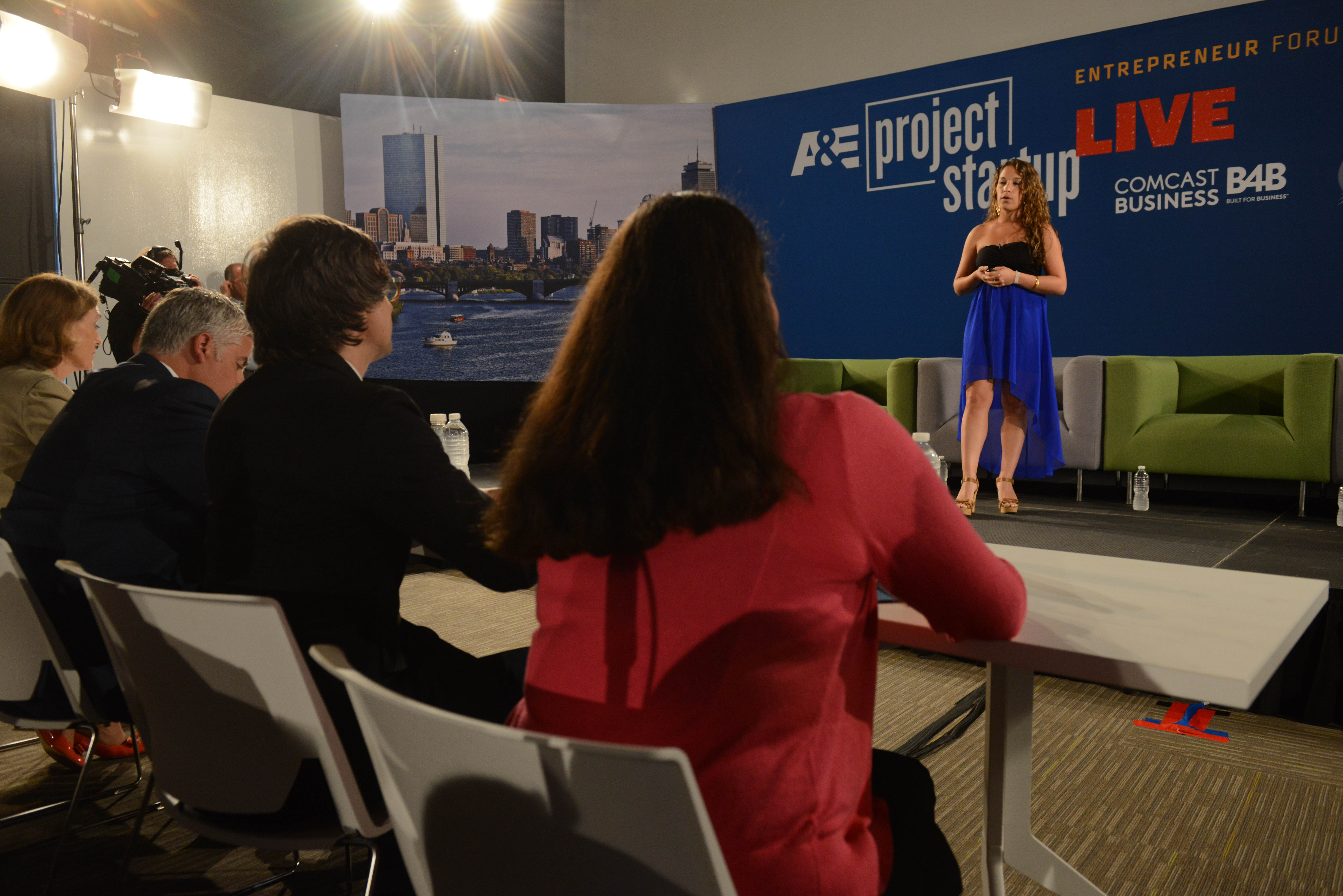 A woman presents her startup idea in front of a panel of judges.