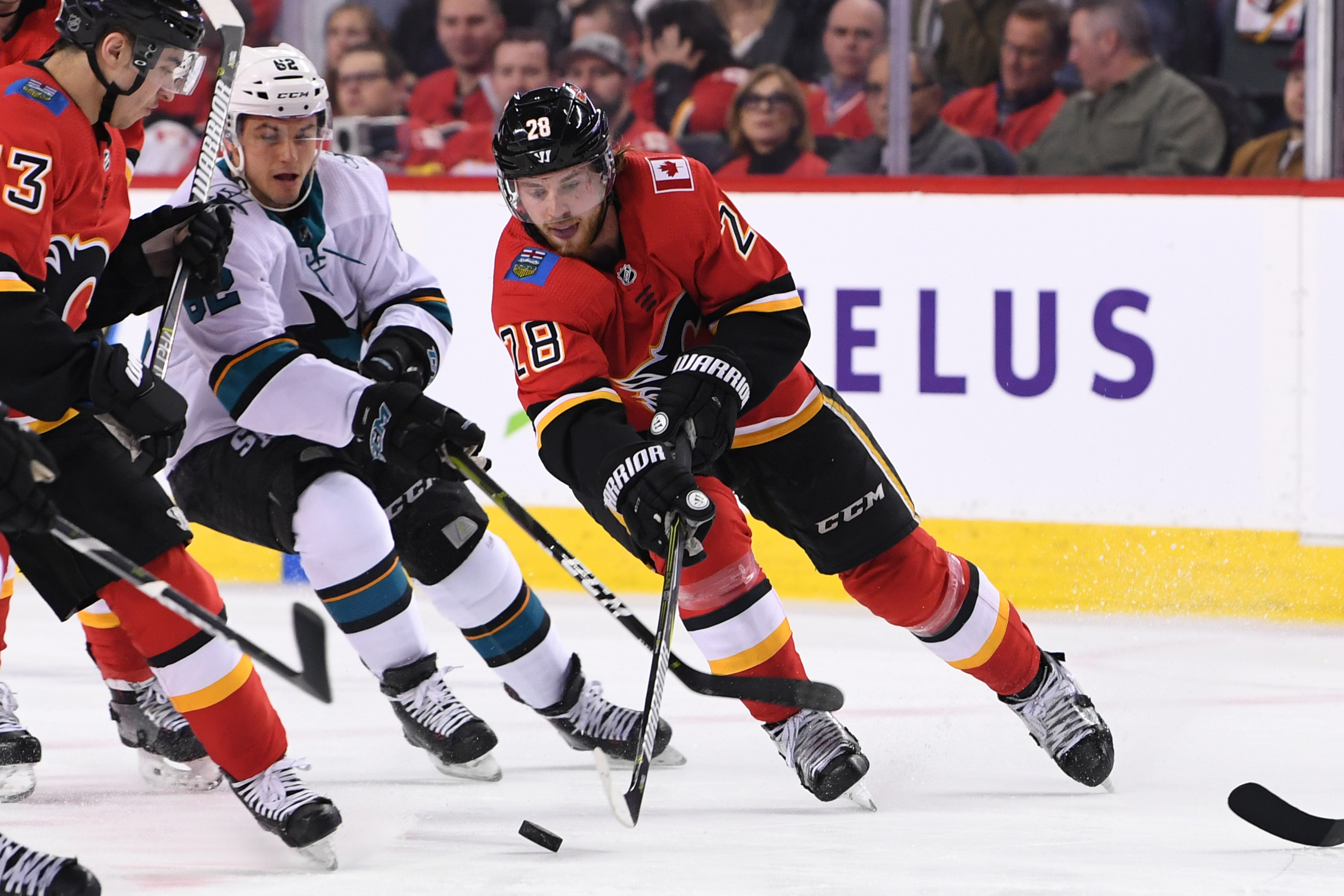 Feb 7, 2019; Calgary, Alberta, CAN; Calgary Flames center Elias Lindholm (28) skates the puck up against San Jose Sharks right wing Kevin Labanc (62) during the first period at Scotiabank Saddledome. Mandatory Credit: Candice Ward