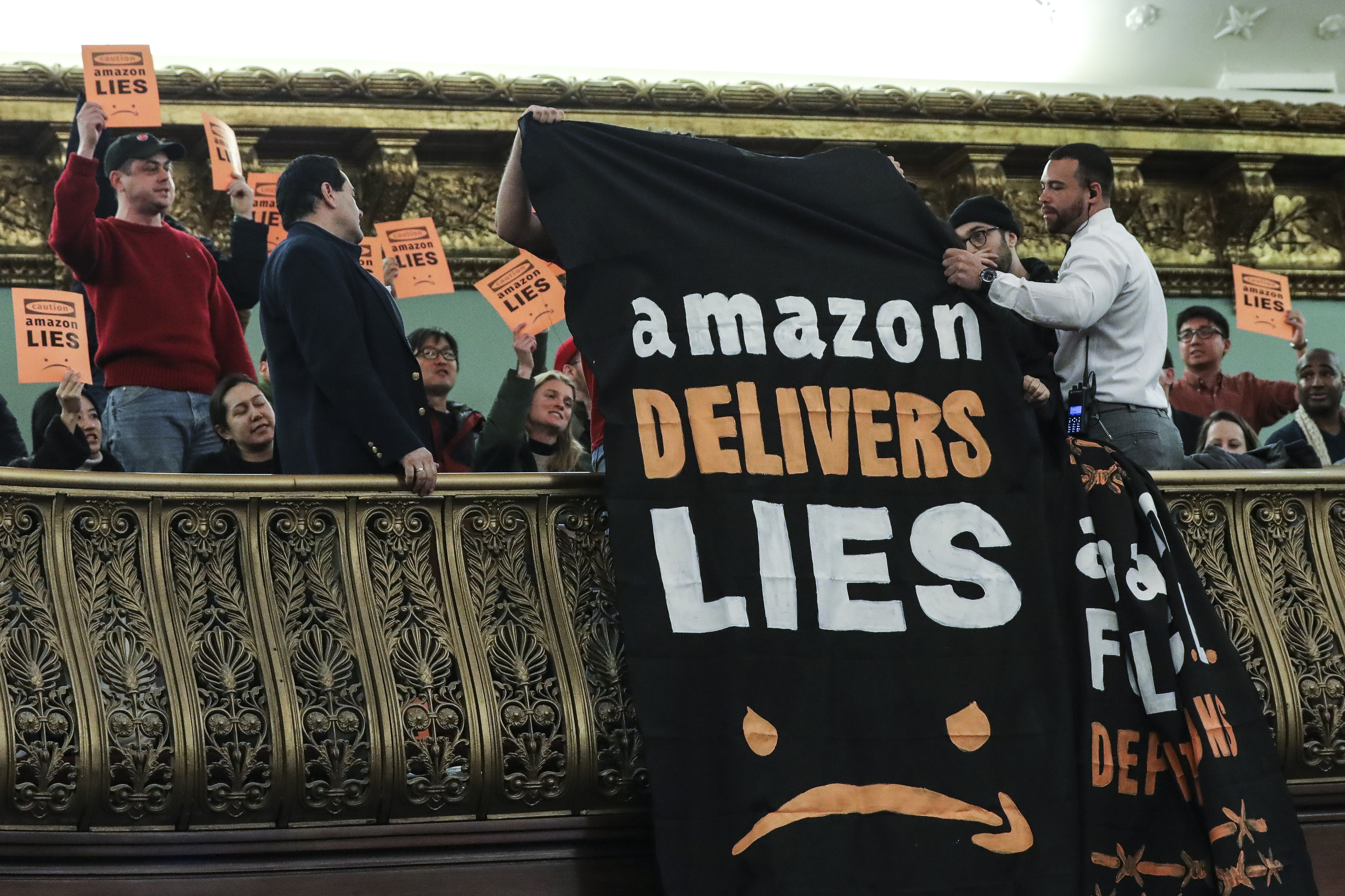 "Protestors unfurl an anti-Amazon banner that reads ""Amazon delivers lies"" from the balcony of a hearing room during a New York City Council Finance Committee hearing at New York City Hall."