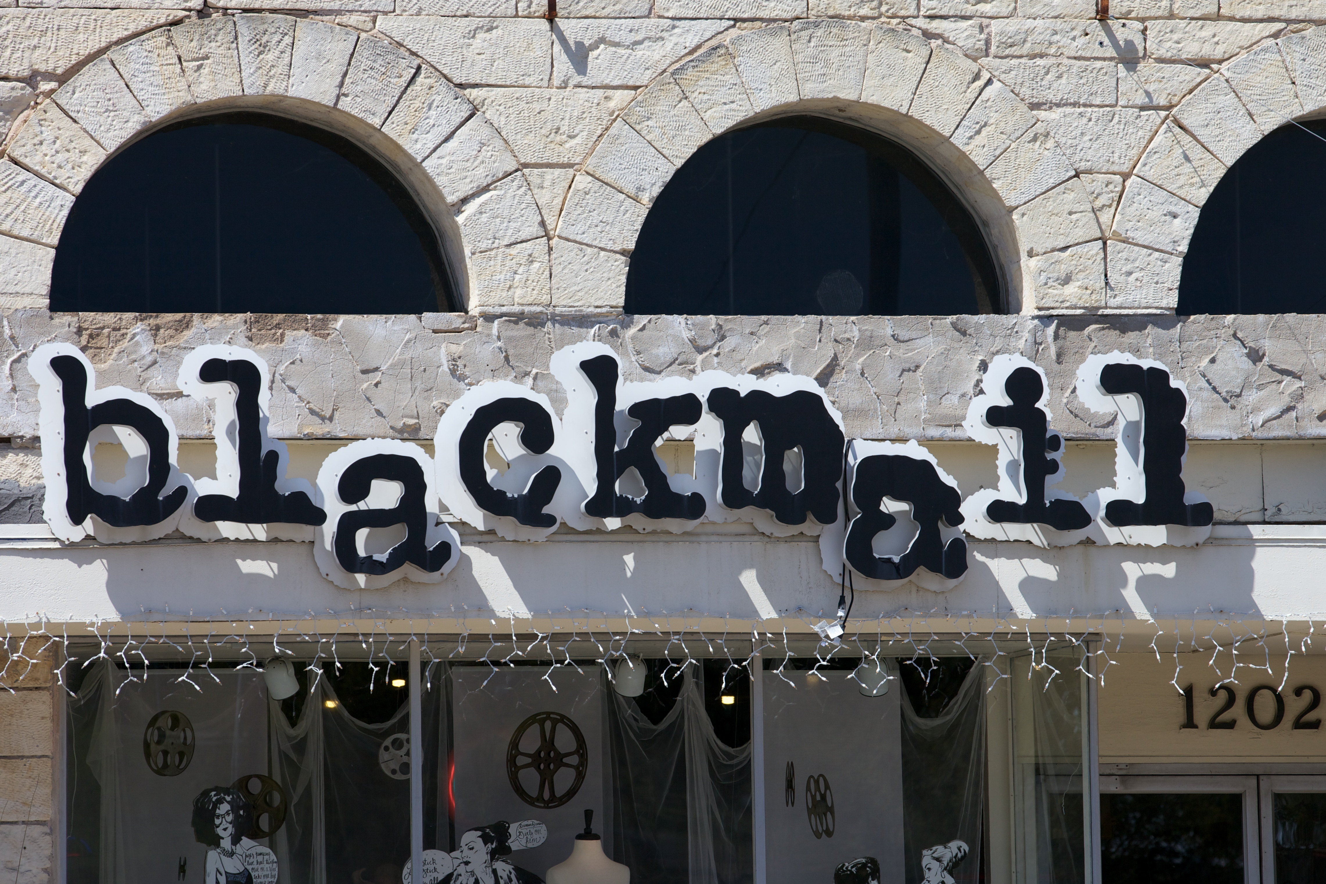 Sign outside limestone building that spells blackmail no caps looks like exploded Courier