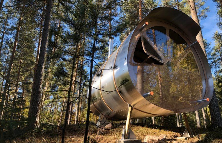 Tiny aluminum cabin in woods.