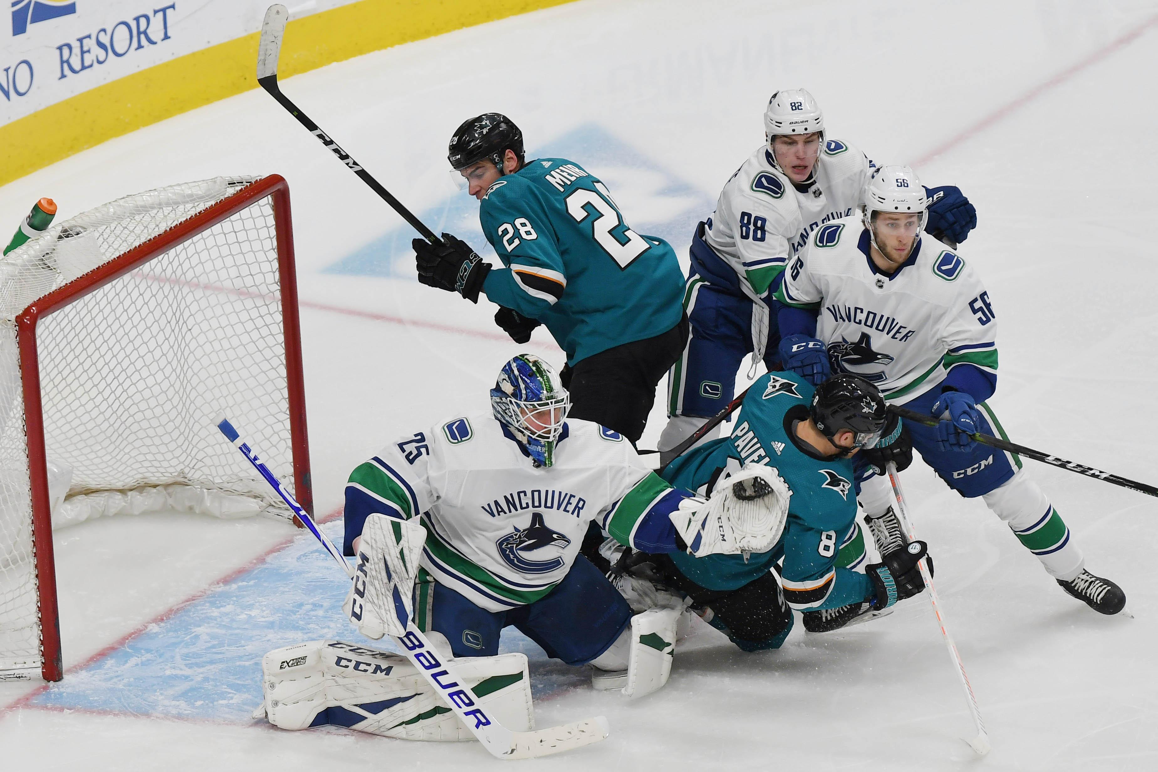 Feb 16, 2019; San Jose, CA, USA; San Jose Sharks center Joe Pavelski (8) collides with Vancouver Canucks goaltender Jacob Markstrom (25) in the second period of their game at SAP Center at San Jose. Mandatory Credit: Robert Edwards
