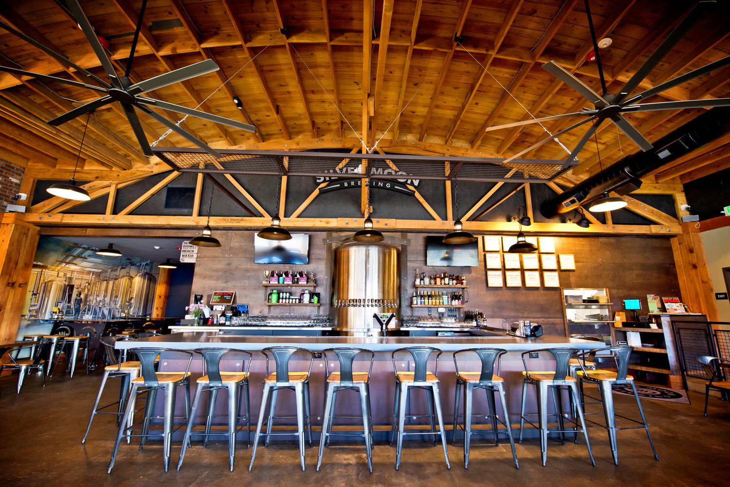 Seven seats at a bar under an arched wooden roof