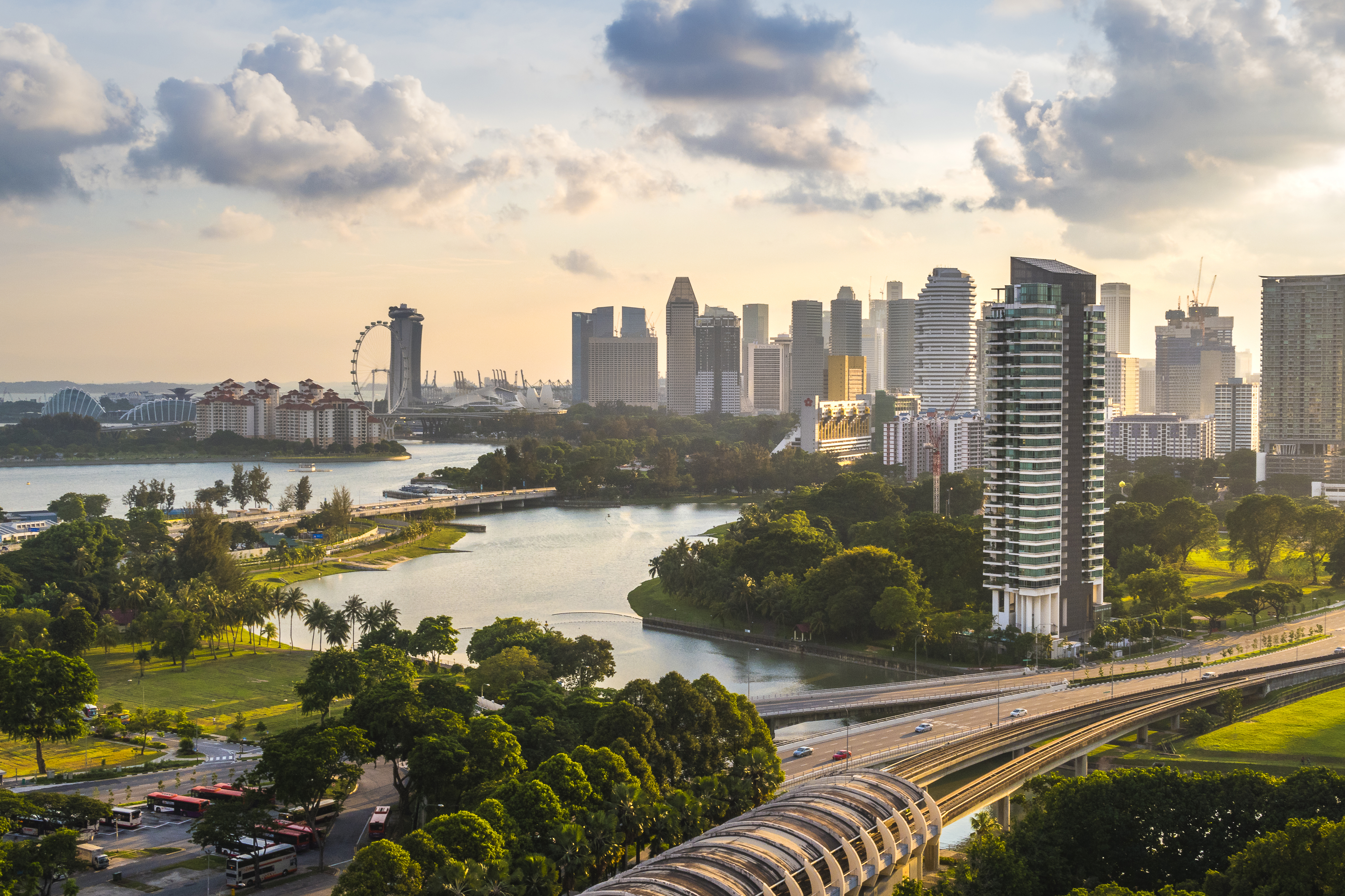 An aerial view of Singapore. There is a highway, trees, and many city buildings.